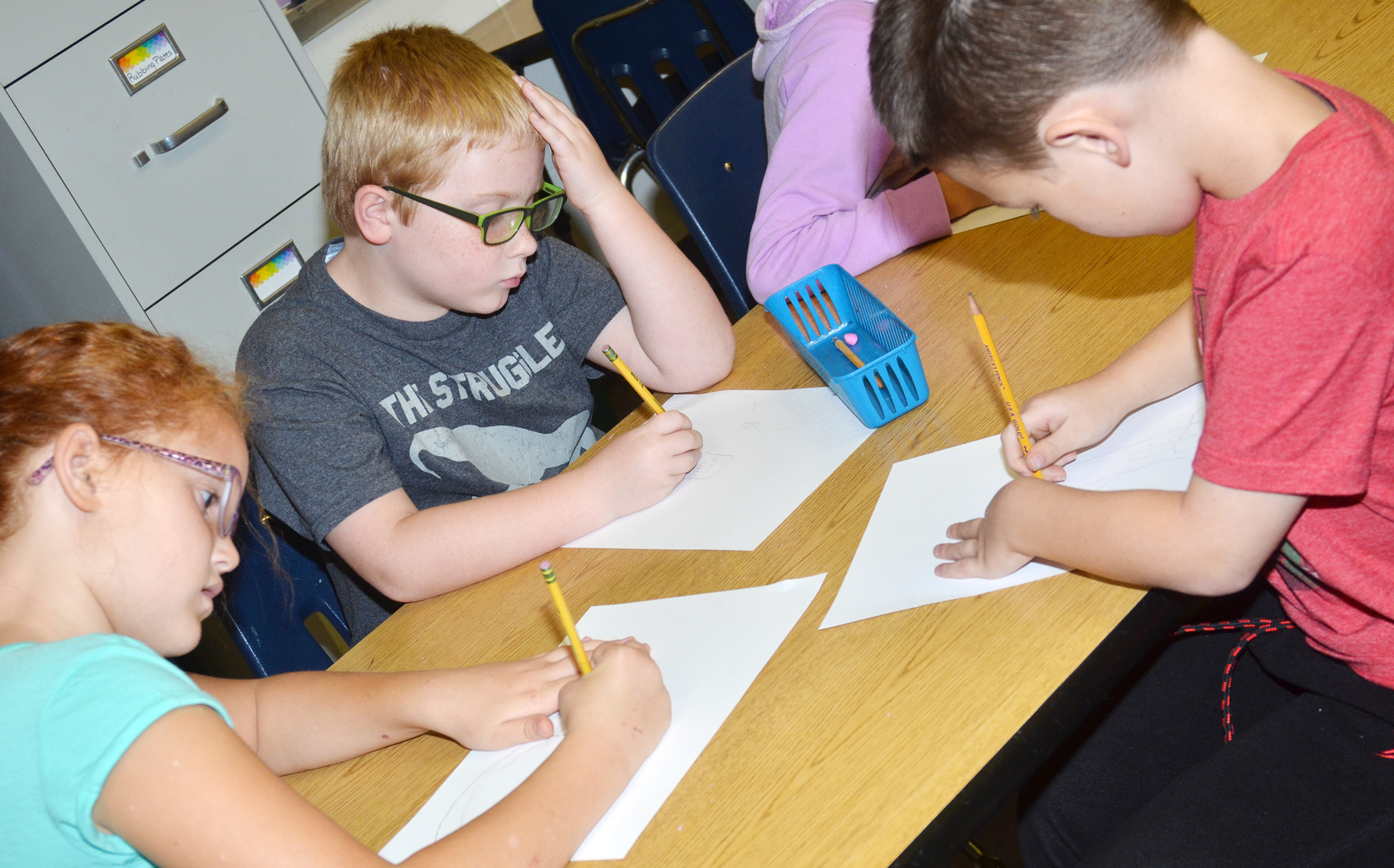 CES third-graders, from left, Analeigh Foster, Aidan Bowles and Mark Lawson draw their still lifes.