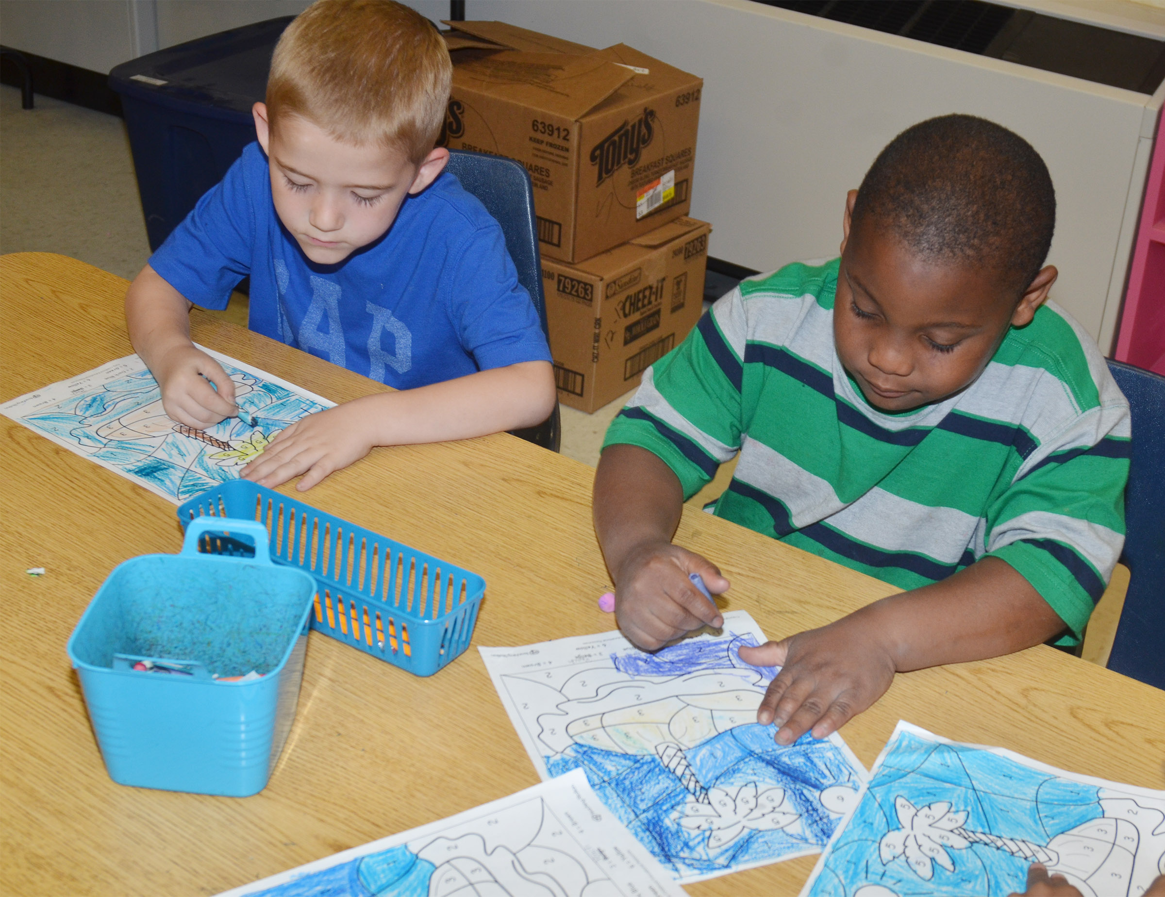 CES kindergarteners Mason Edwards, at left, and Malachi Conner color their beach drawings.