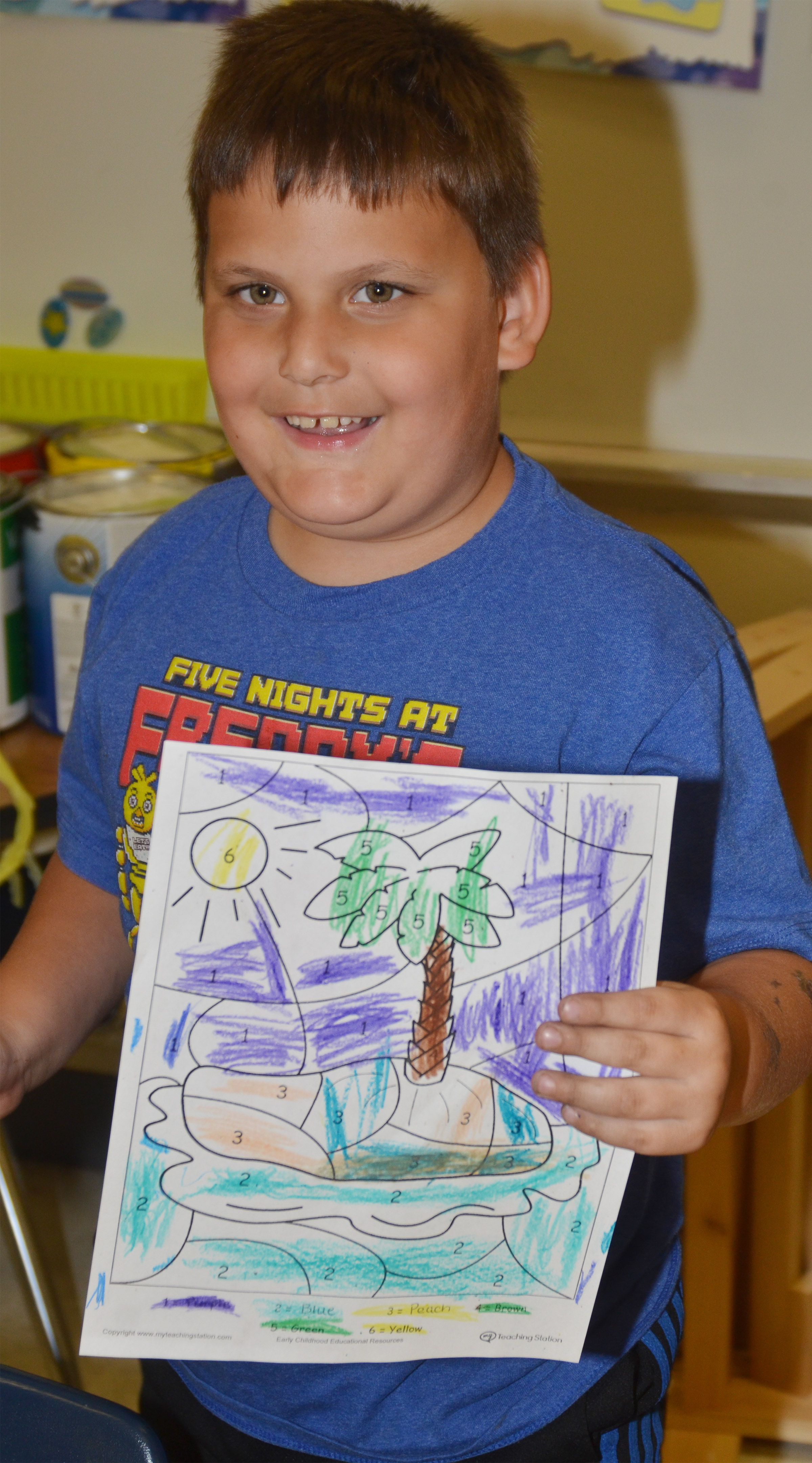 CES kindergartener Cloud Malone holds his beach drawing.