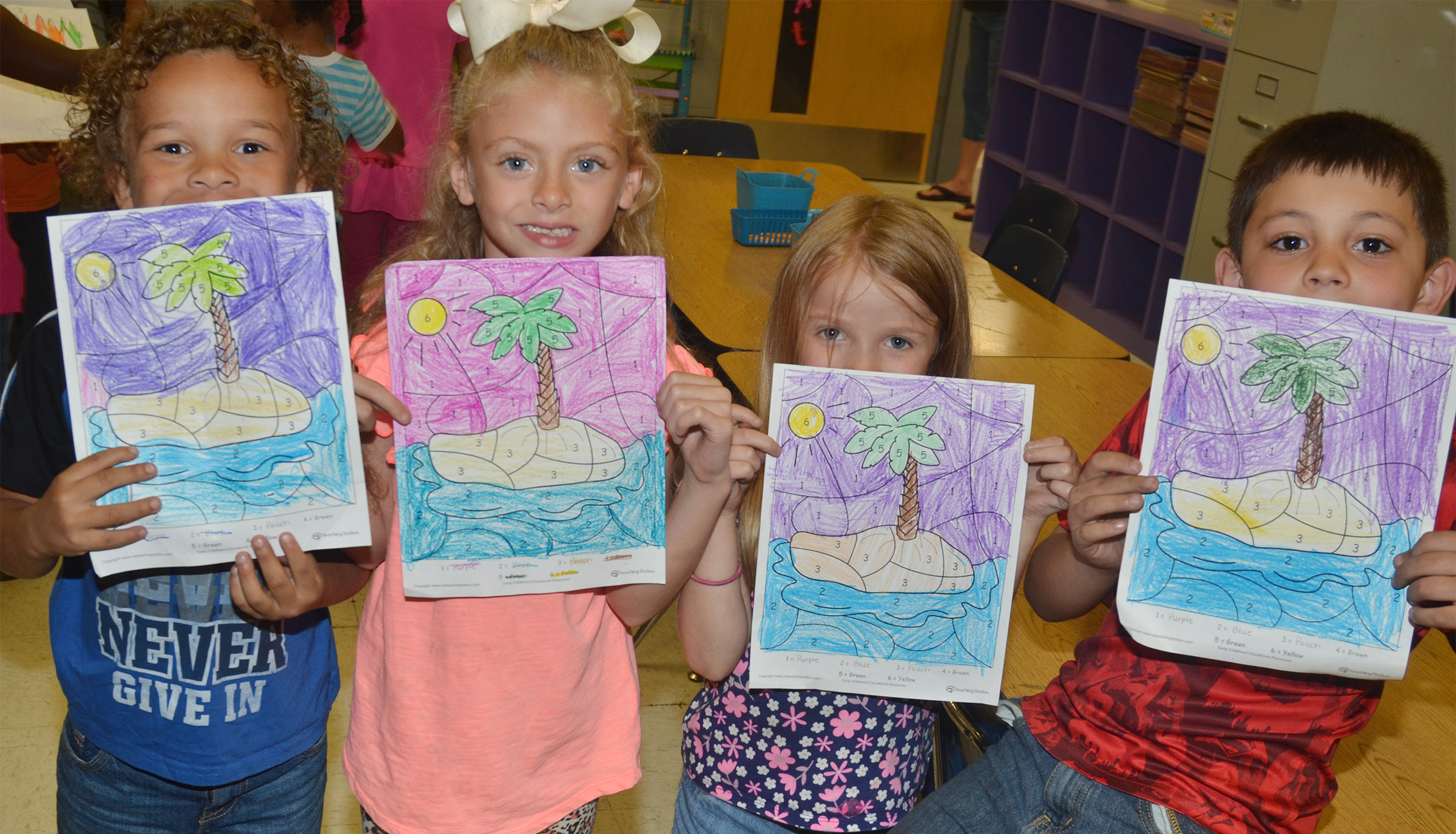 From left, CES kindergarteners Dyra Welch, Aliyah Litsey, Leah Covey and Keagan Shearer hold their beach drawings.