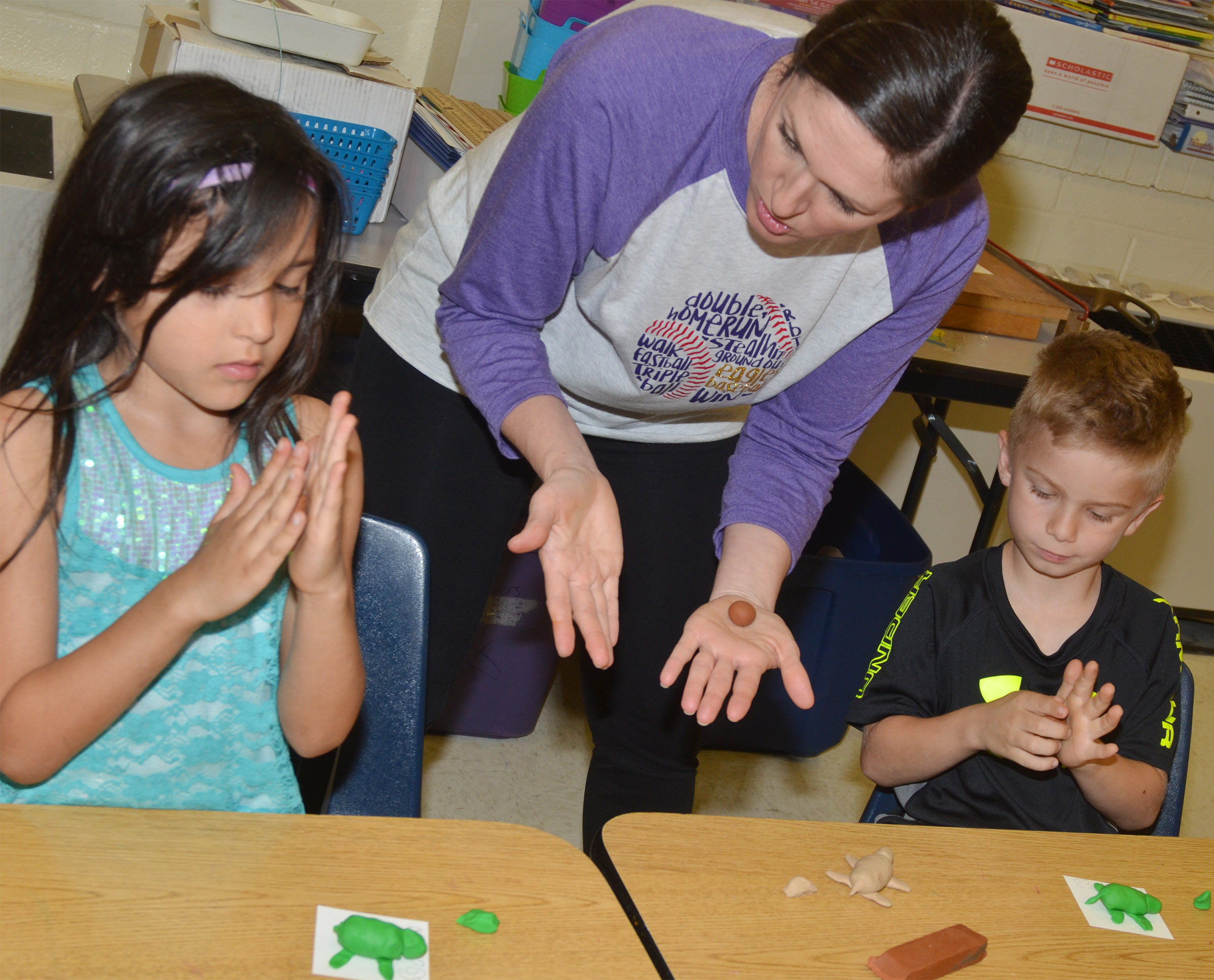 CES art teacher Adrienne Hash helps first-graders Gemma Bledsoe, at left, and Parker Hamilton make their clay turtles.