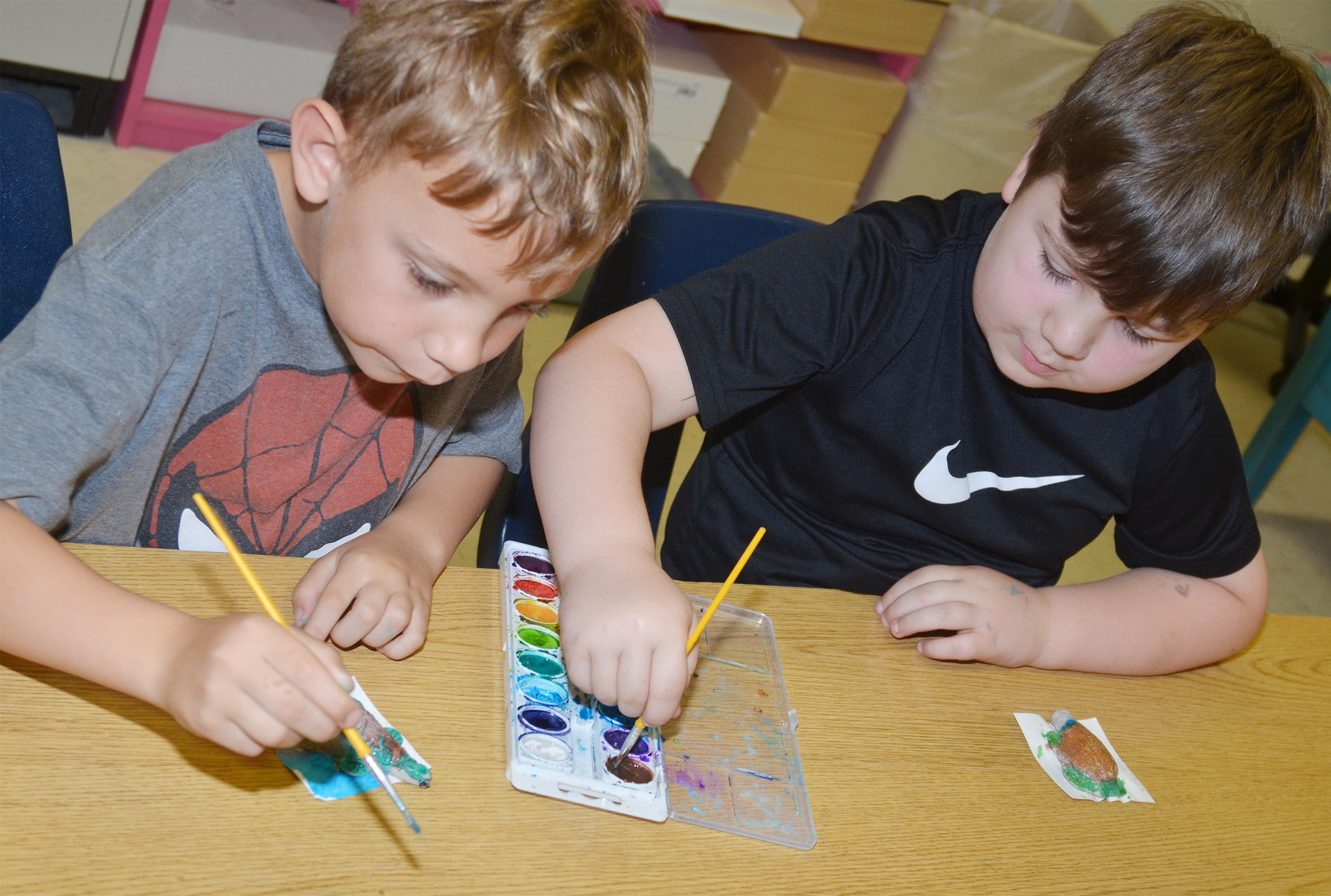 CES first-graders Gabe Prior, at left, and Luke Mardis paint their turtles.
