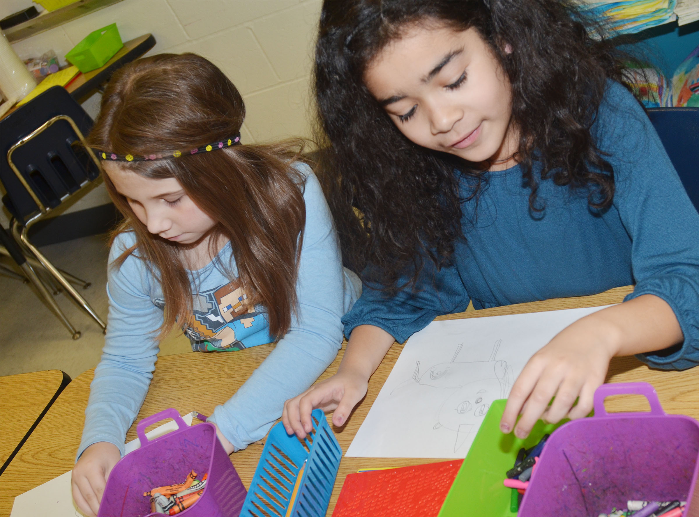 CES second-graders Natalia West, at left, and Sophia Santos draw their animal drawings.