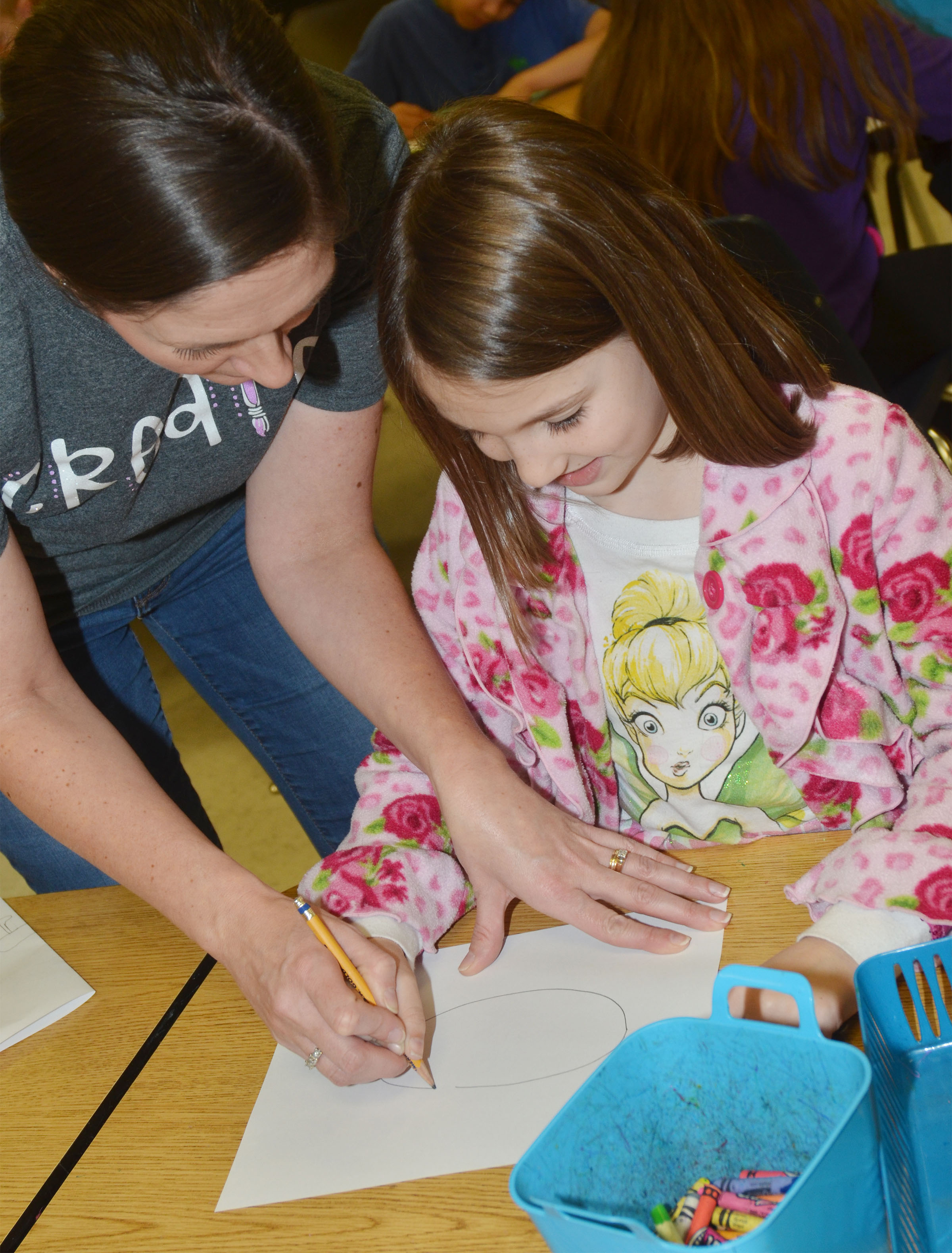 CES art teacher Adrienne Hash helps second-grader Kairi Tucker draw her animal drawing.