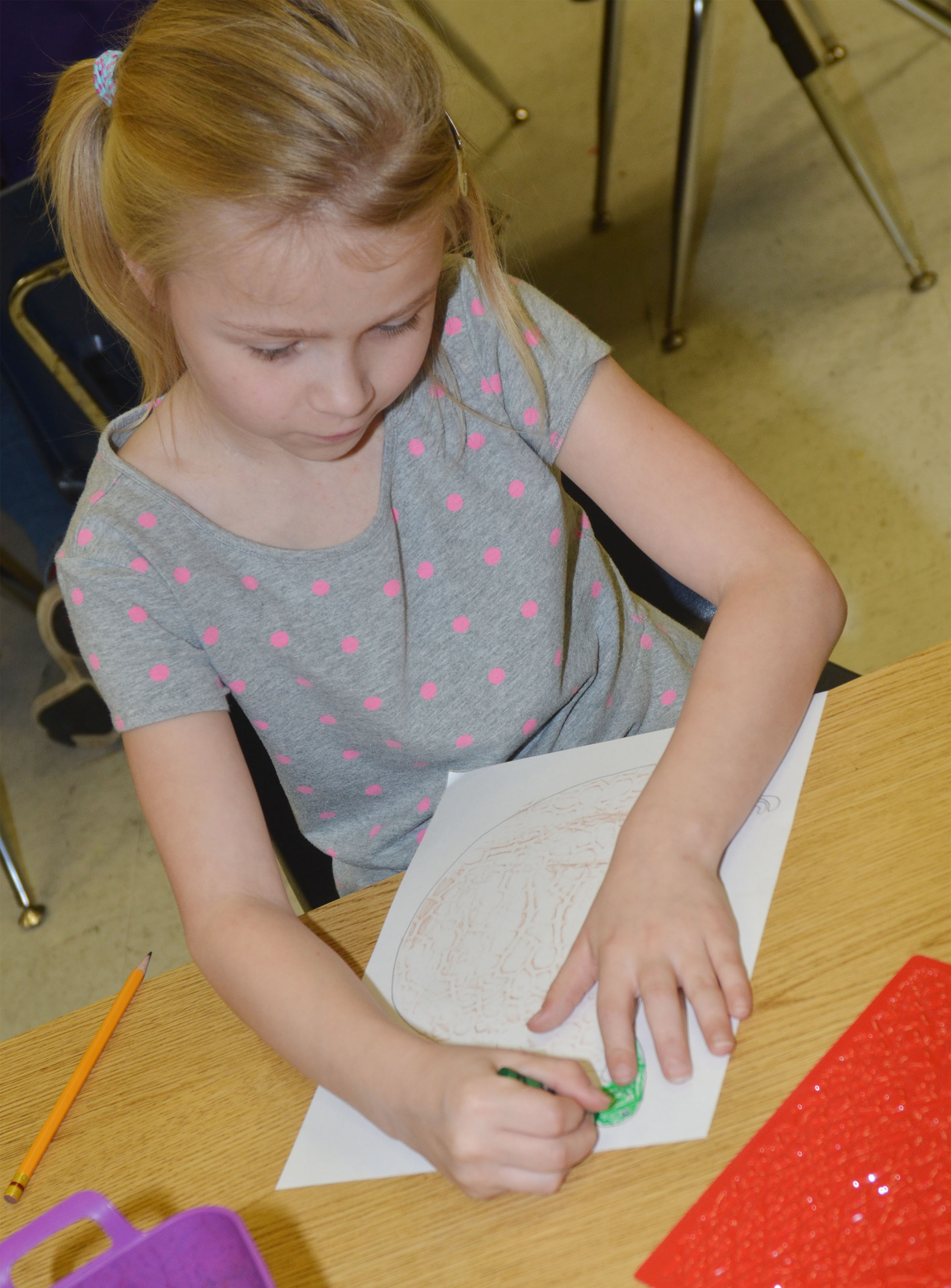 CES second-grader Lacy Covey adds texture to her animal drawing.