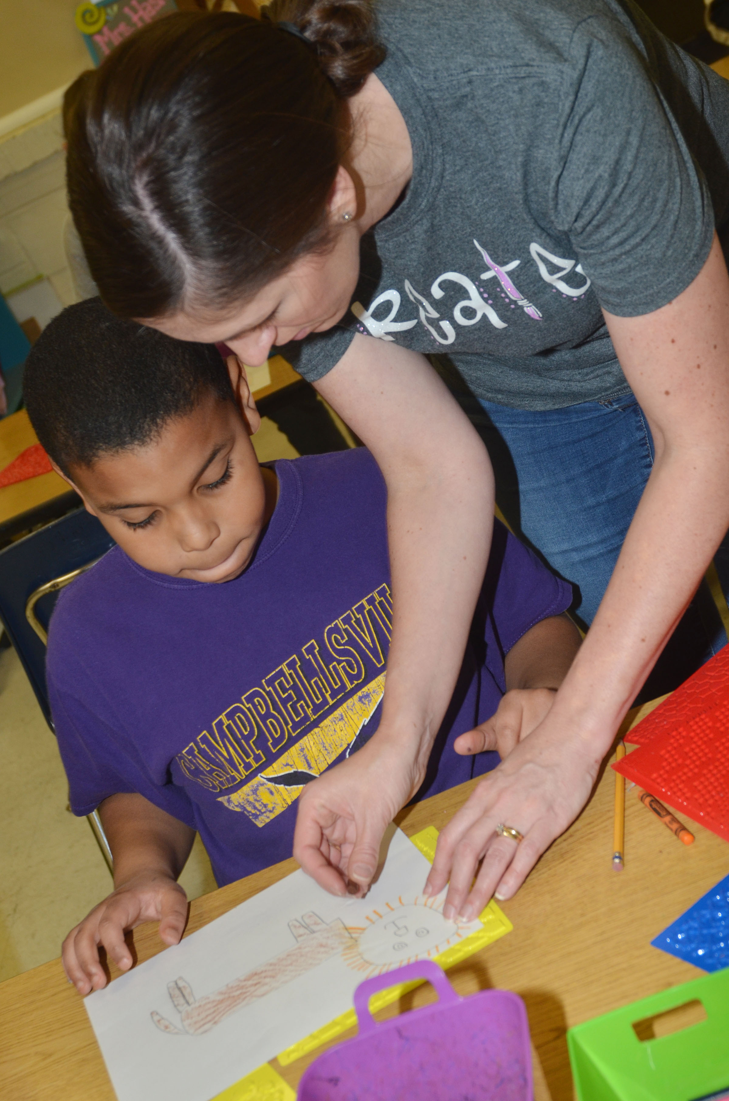 CES art teacher Adrienne Hash helps second-grader Zaemar Hoskins add texture to his lion drawing.