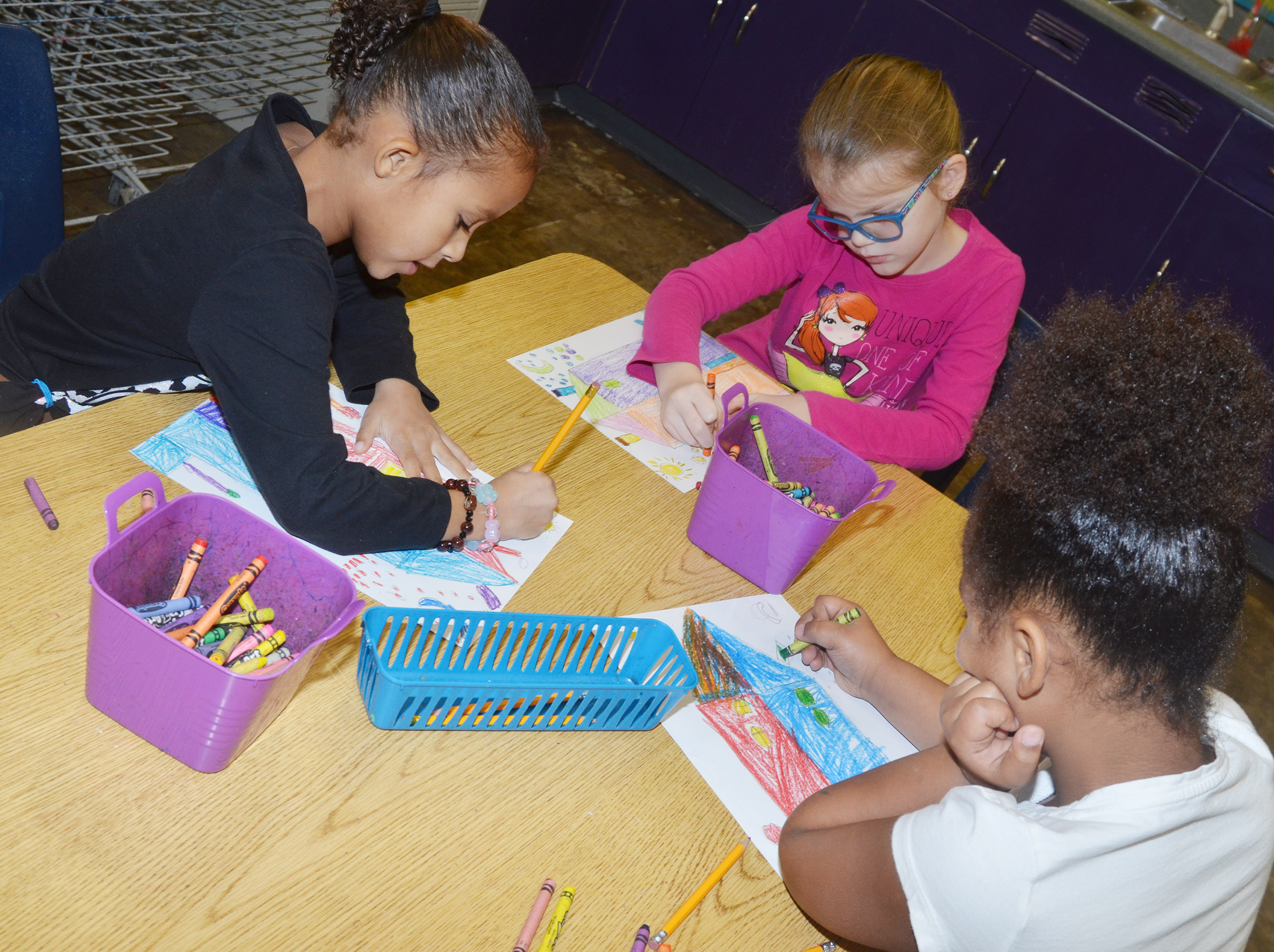 From left, CES first-graders Aleja Taylor, Zoe Weddle and Raelin Goddard color their warm and cool color houses.