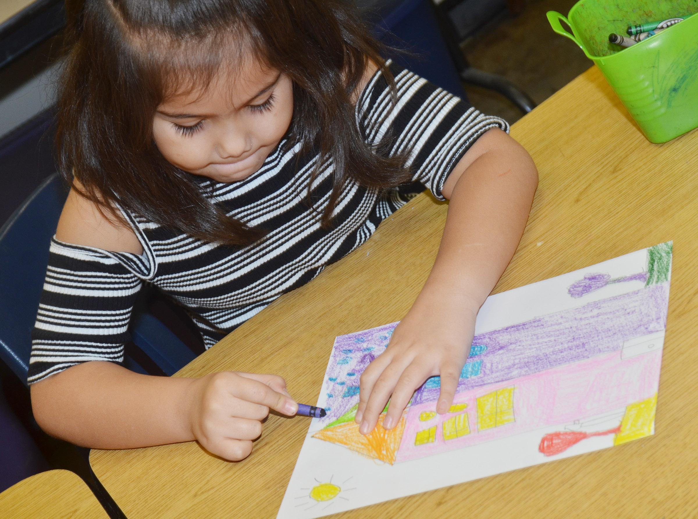 CES first-grader Hannah Matias colors her warm and cool color house.