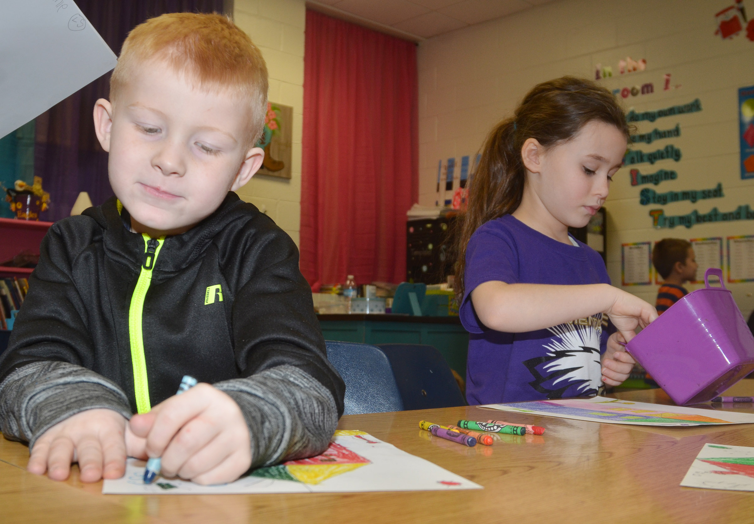 CES first-graders Jayden Maupin, at left, and Stella Newcomb color their warm and cool color houses.