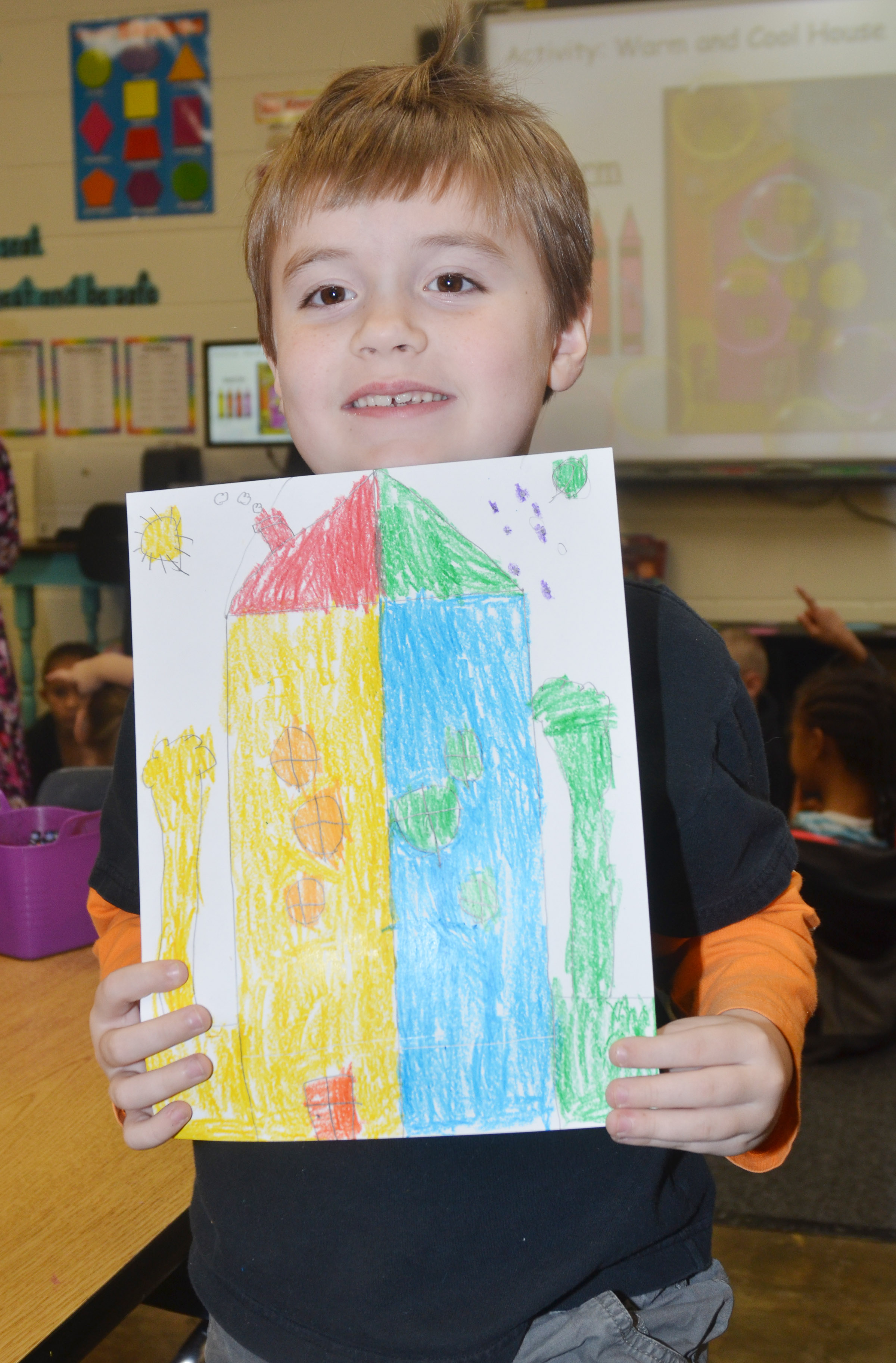 CES first-grader Gavin Williams holds his finished warm and cool color house.