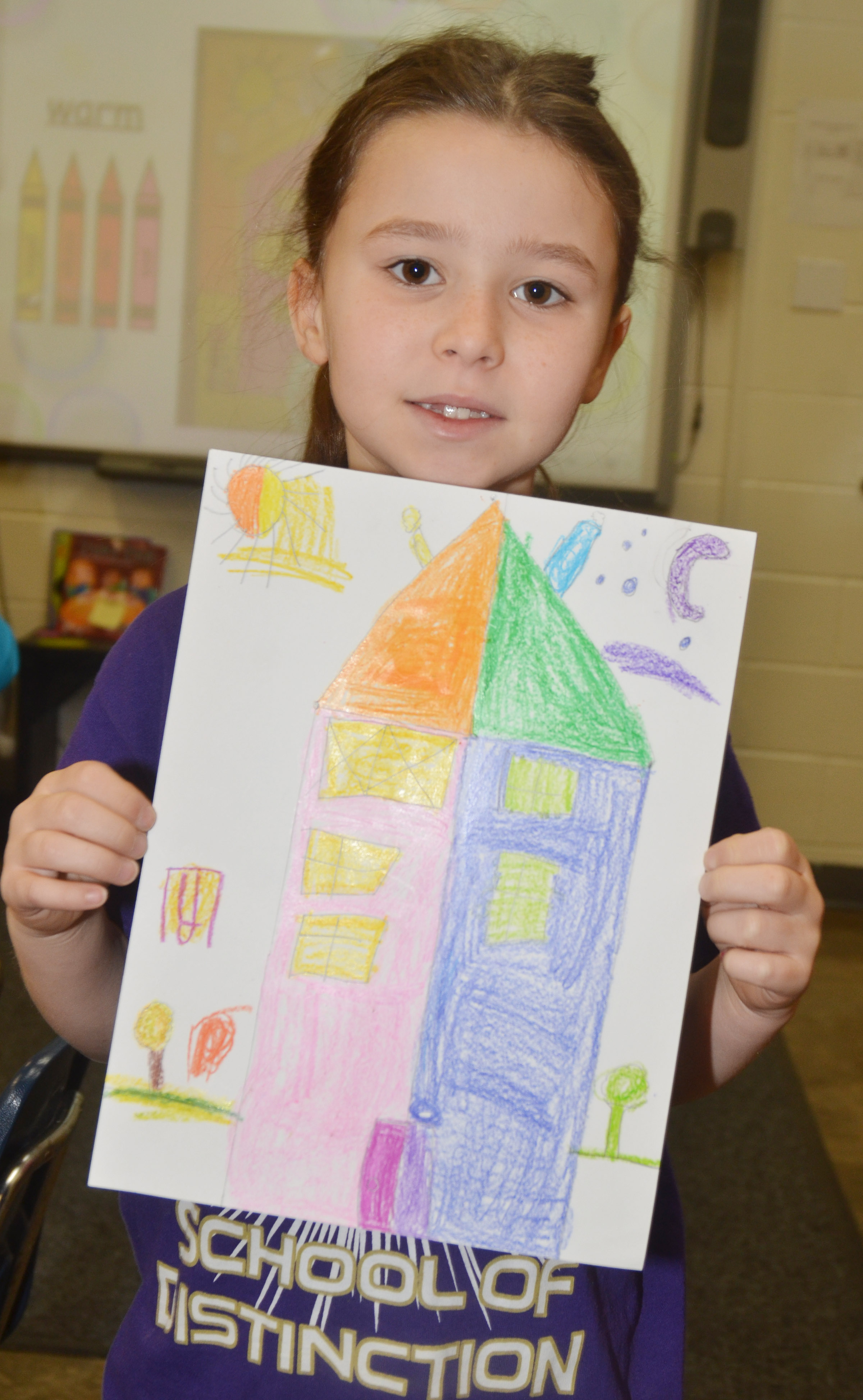 CES first-grader Stella Newcomb holds her finished warm and cool color house.