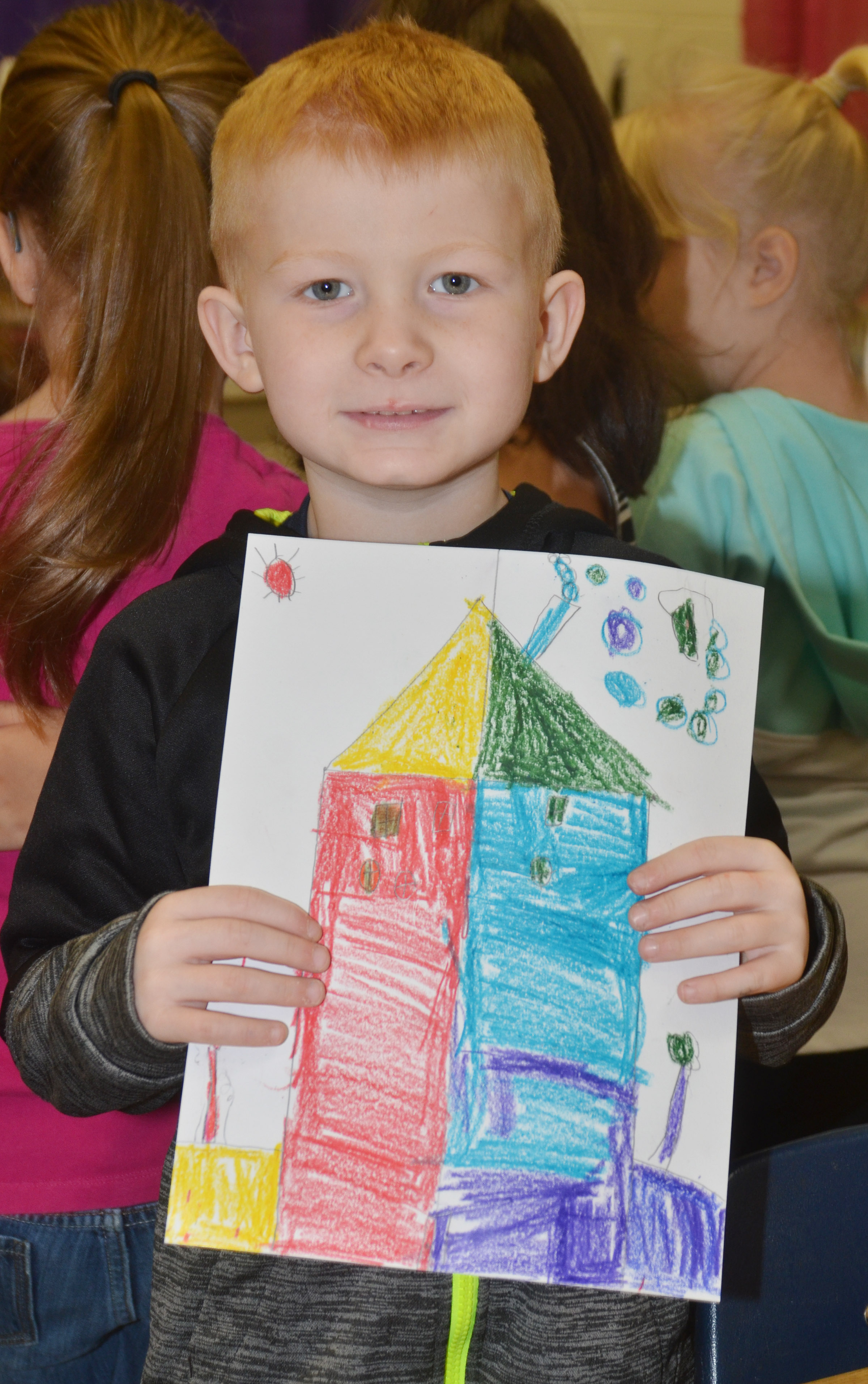 CES first-grader Jayden Maupin holds his finished warm and cool color house.