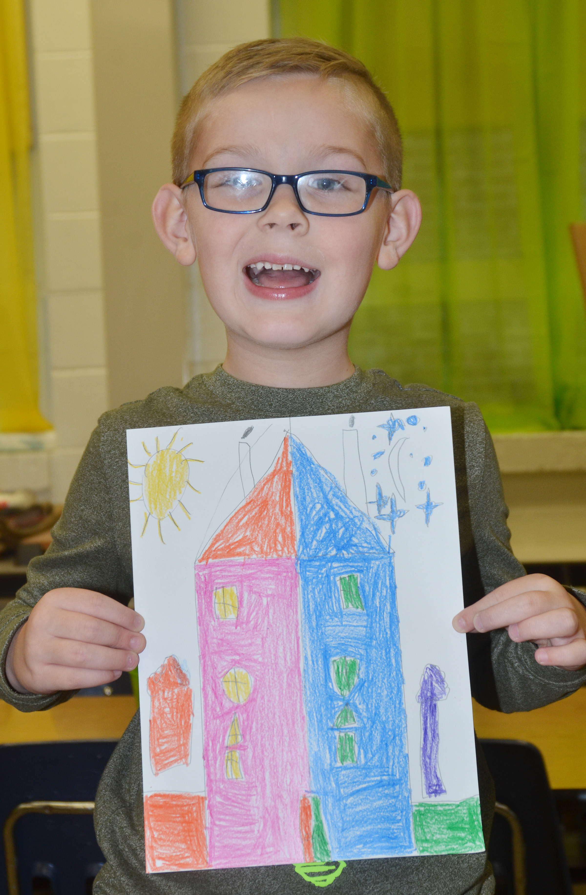 CES first-grader John Hagan Newton holds his finished warm and cool color house.