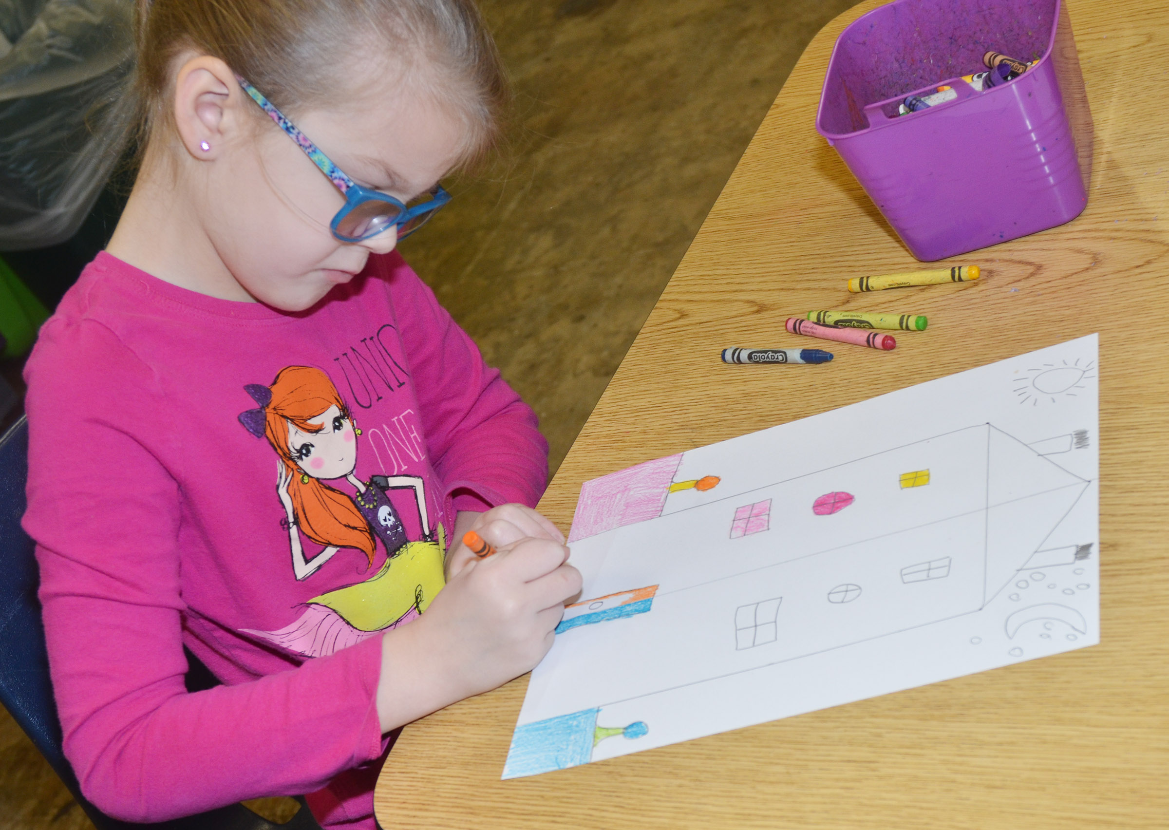 CES first-grader Zoe Weddle colors her warm and cool color house.