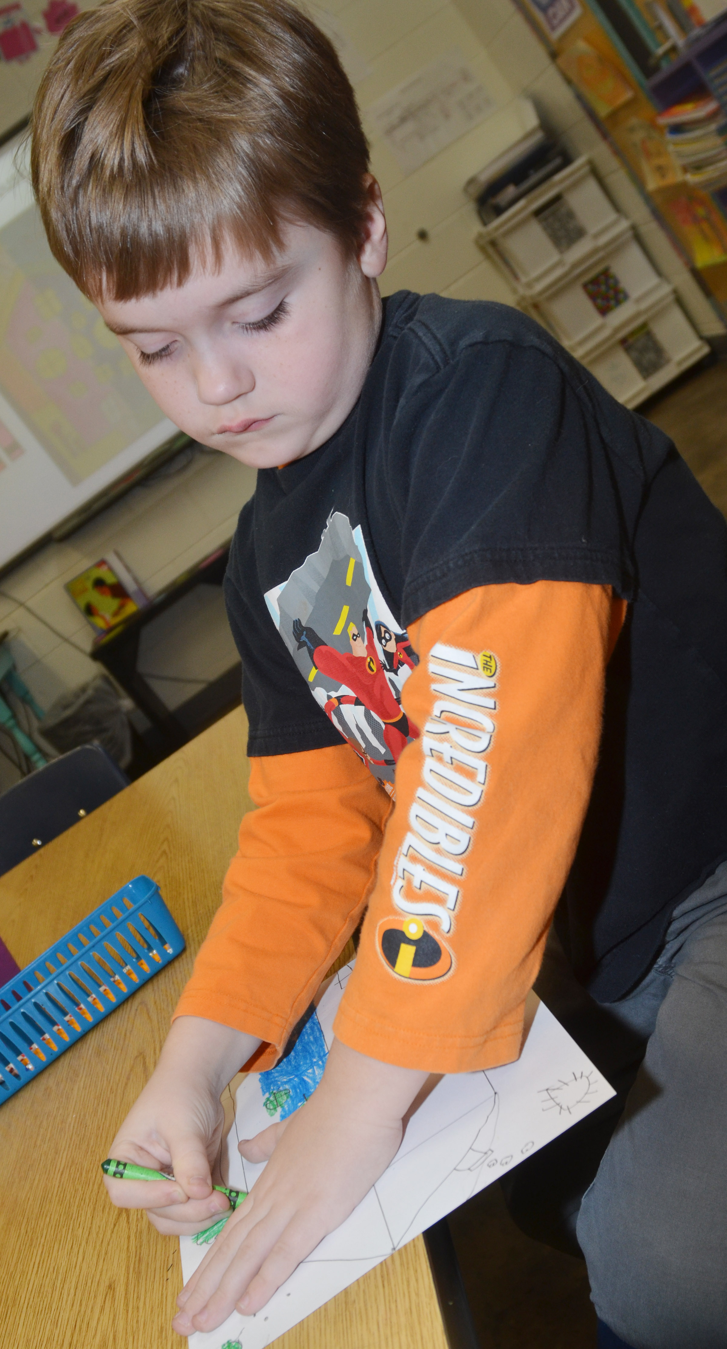 CES first-grader Gavin Williams colors his warm and cool color house.