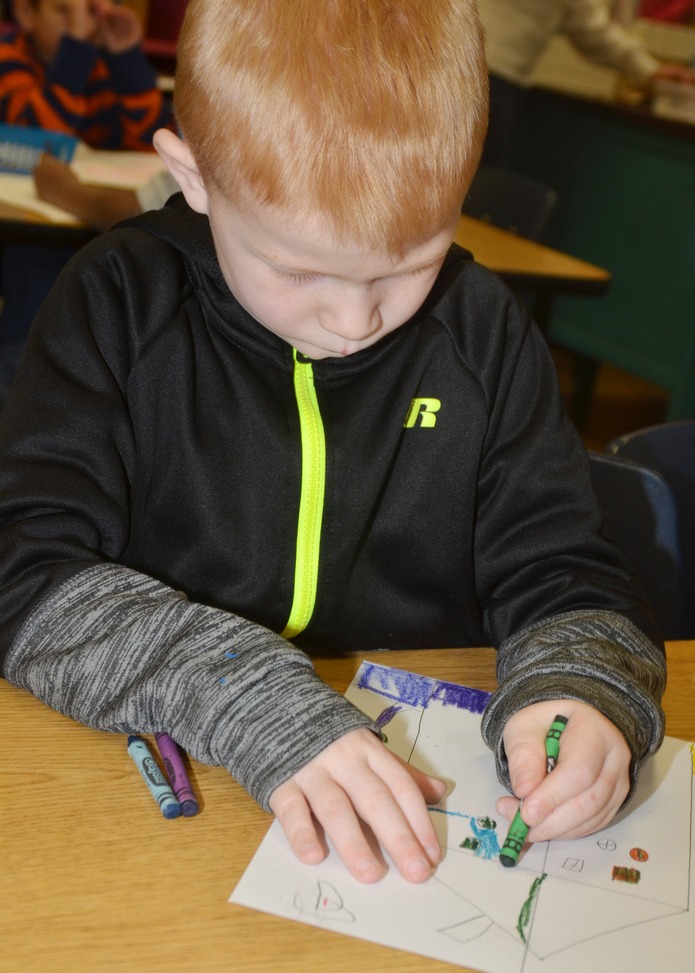 CES first-grader Jayden Maupin colors his warm and cool color house.
