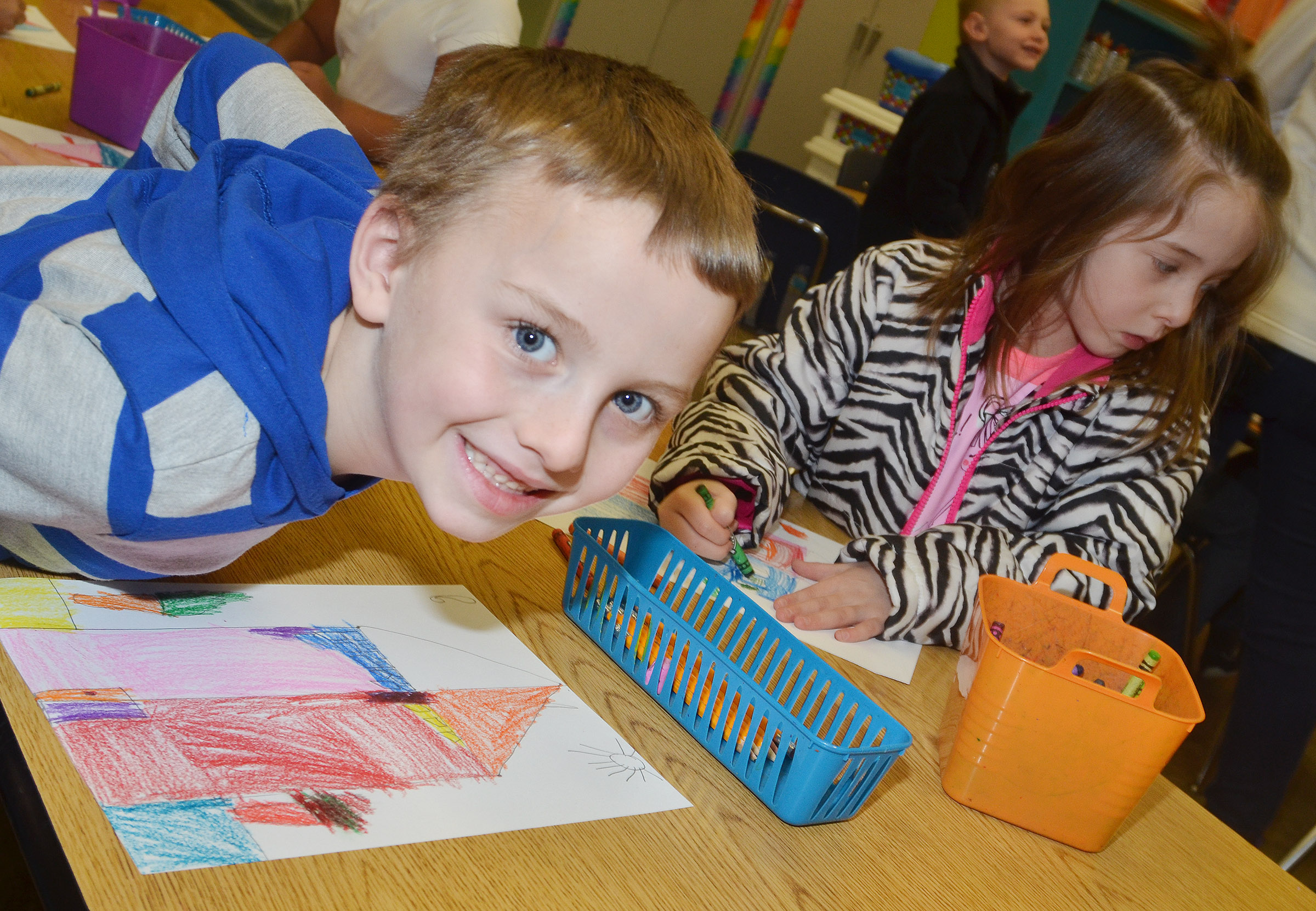 CES first-grader Ronnie Allen smiles as he creates his warm and cool color house.