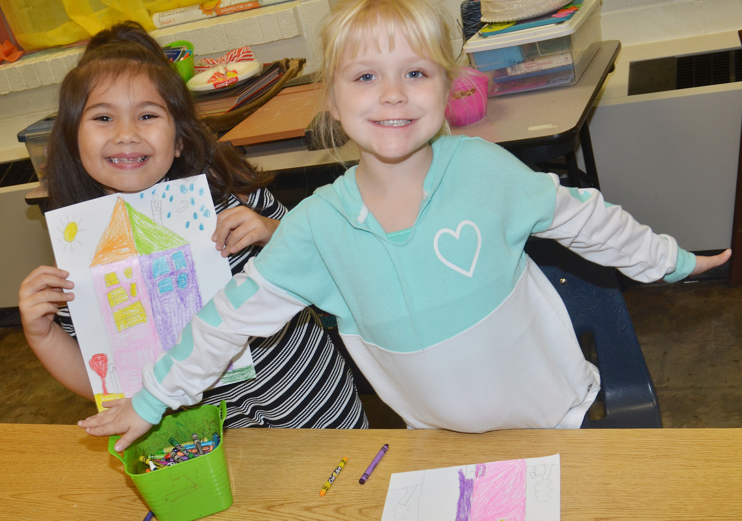CES first-graders Hannah Matias, at left, and Ava Bennett-Marr show off their warm and cool color houses.