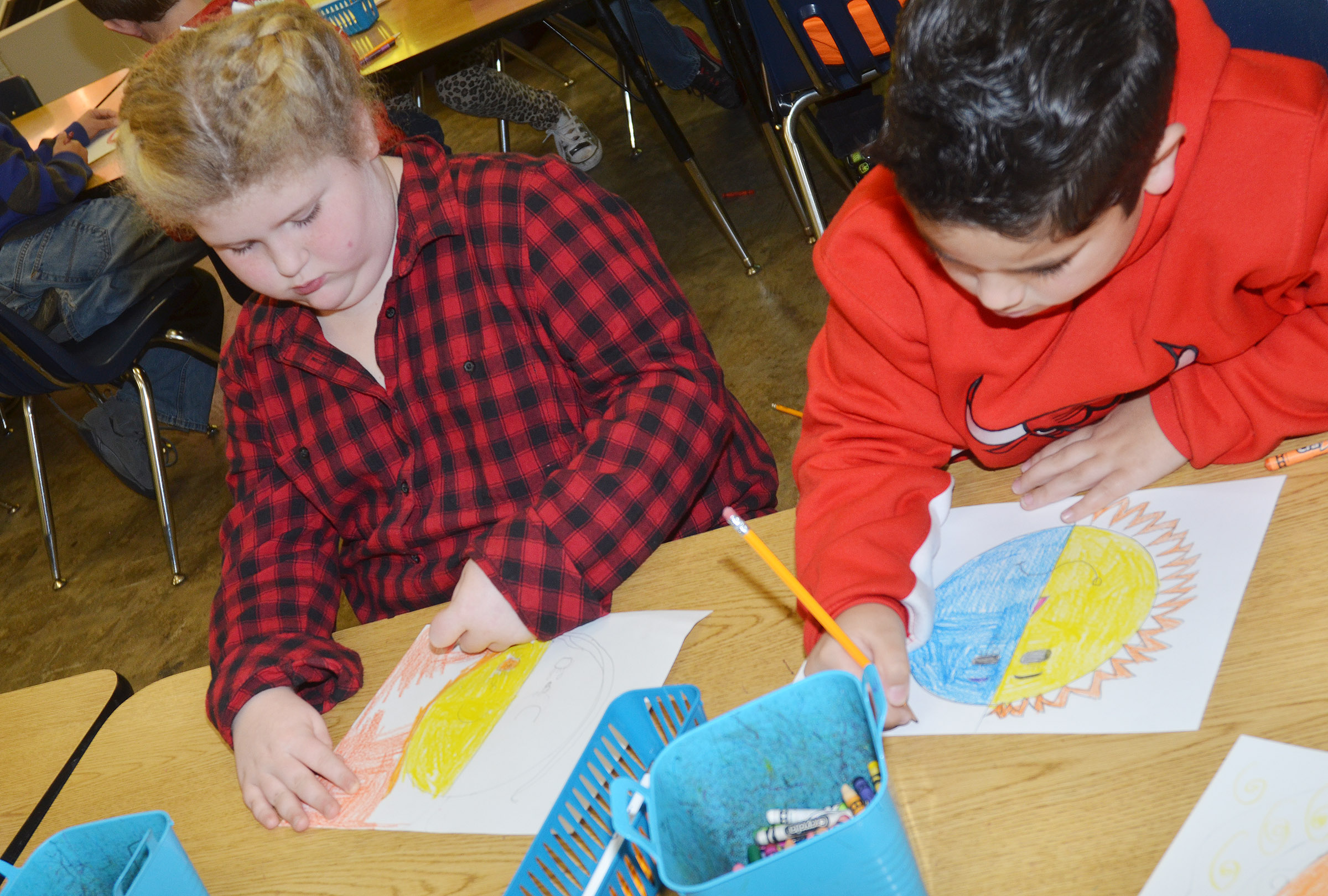 CES second-graders Elizabeth Foster, at left, and Nicholas Almeida color their warm and cool color faces.