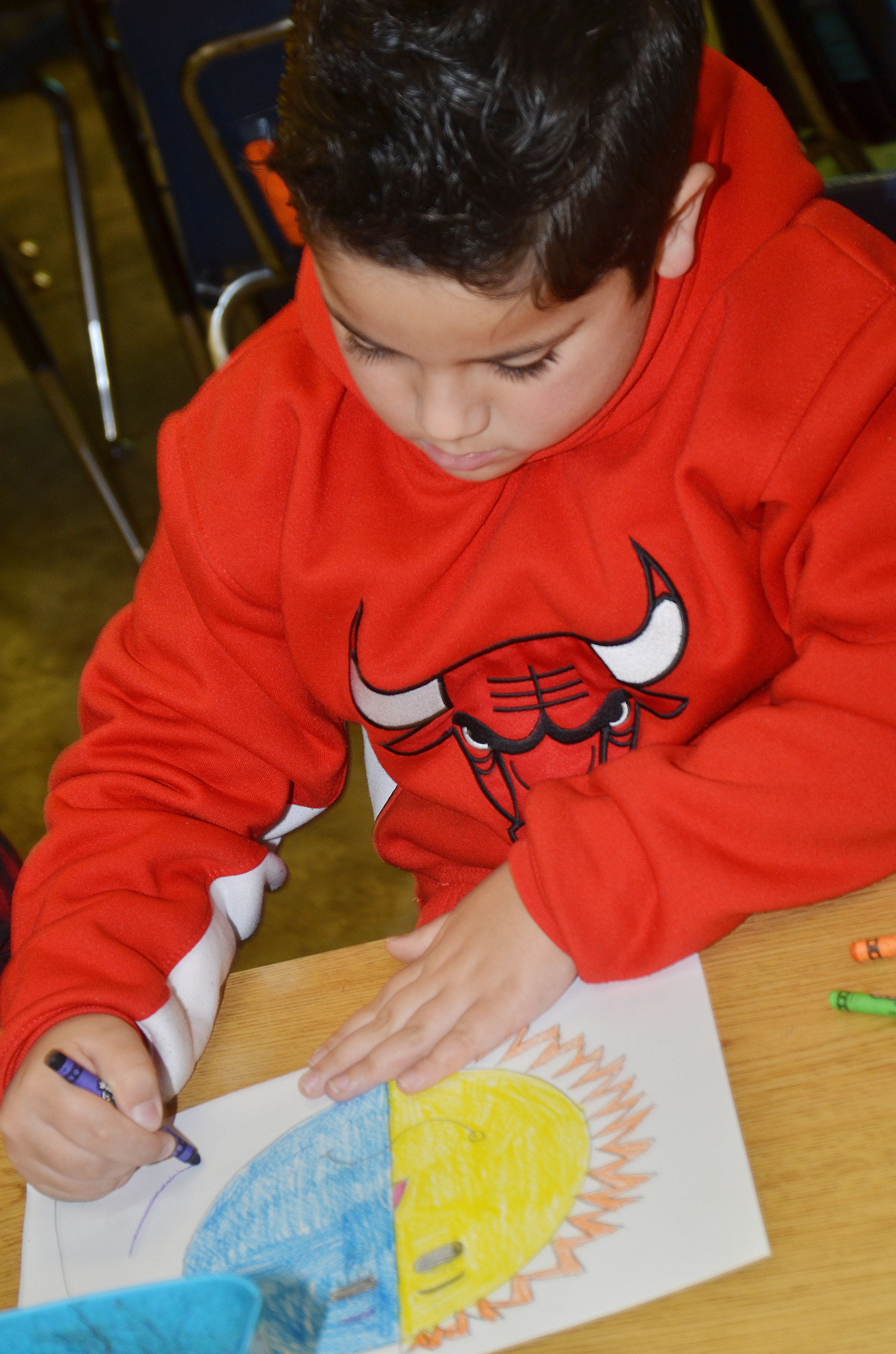 CES second-grader Nicholas Almeida colors his warm and cool color face.