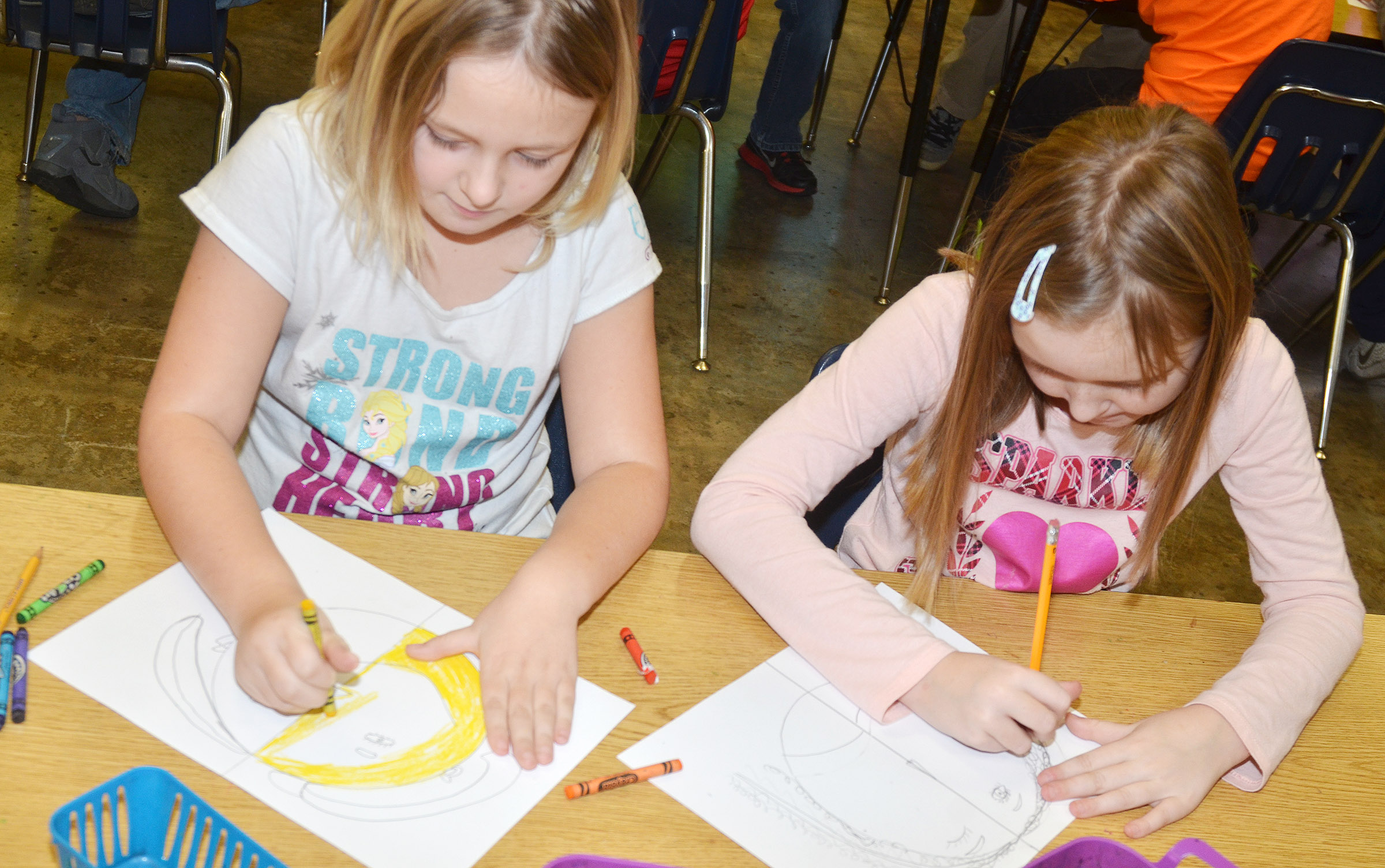 CES second-graders Allison Dean, at left, and Gracie Murphy color their warm and cool color faces.