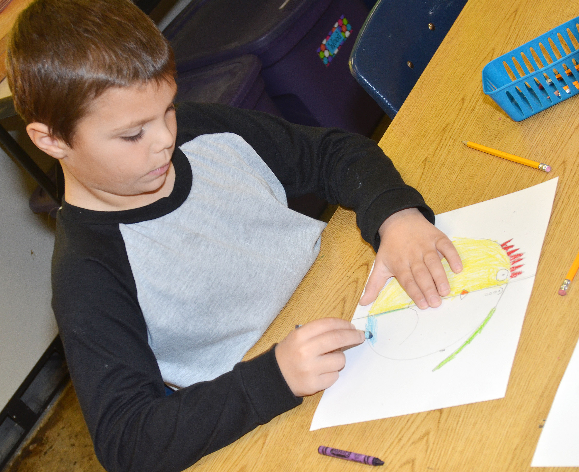CES second-grader Jaxson Hunt colors his warm and cool color face.