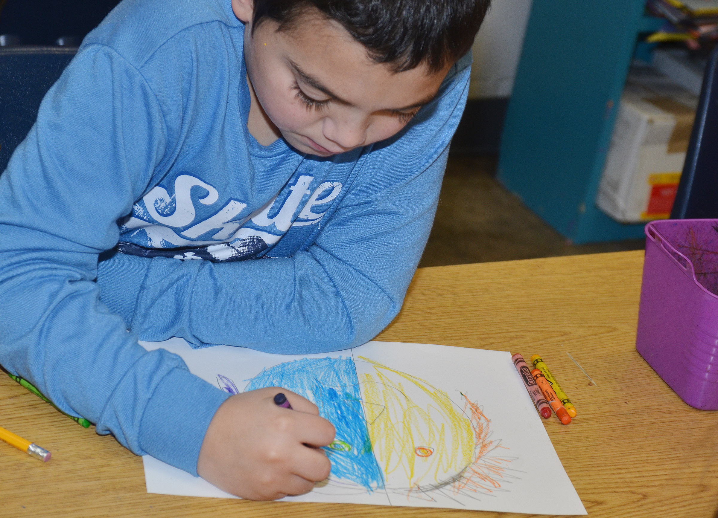 CES second-grader Diego Aquino colors his warm and cool color face.