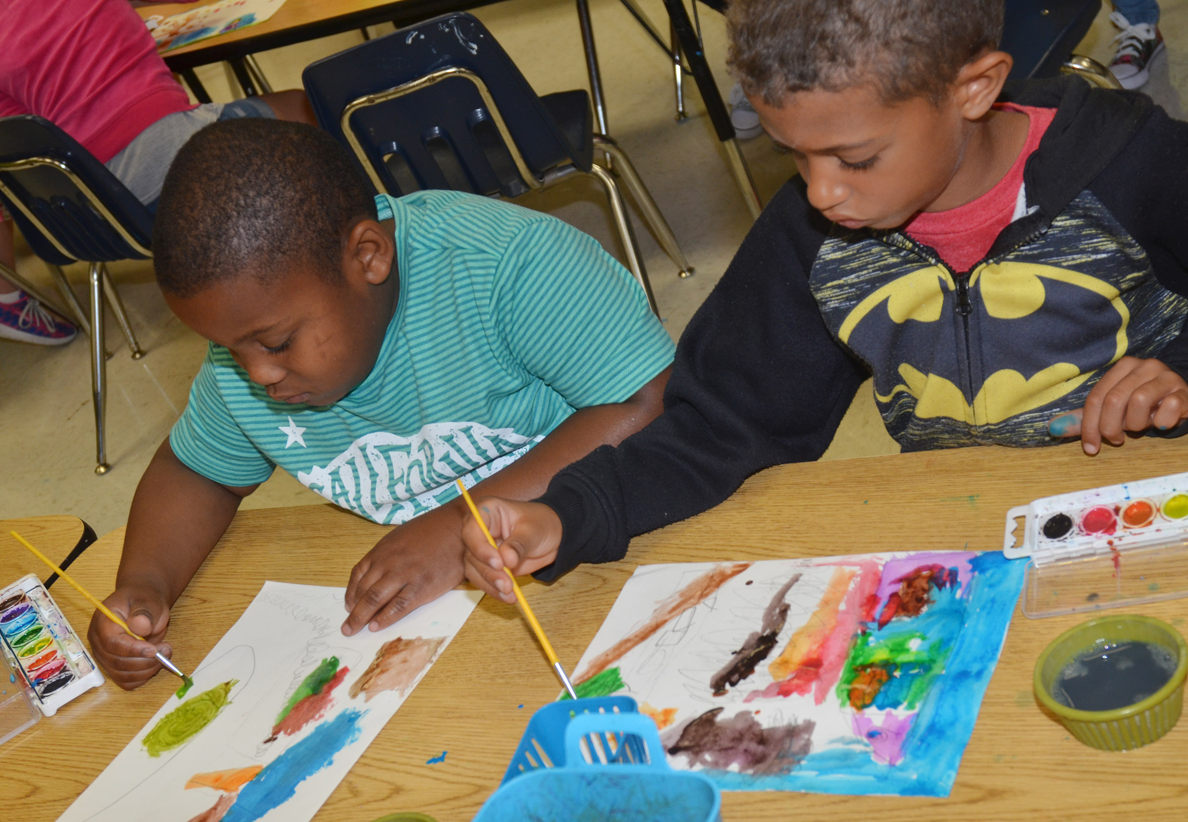 CES first-graders Malachi Conner, at left, and Tyce Owens paint.