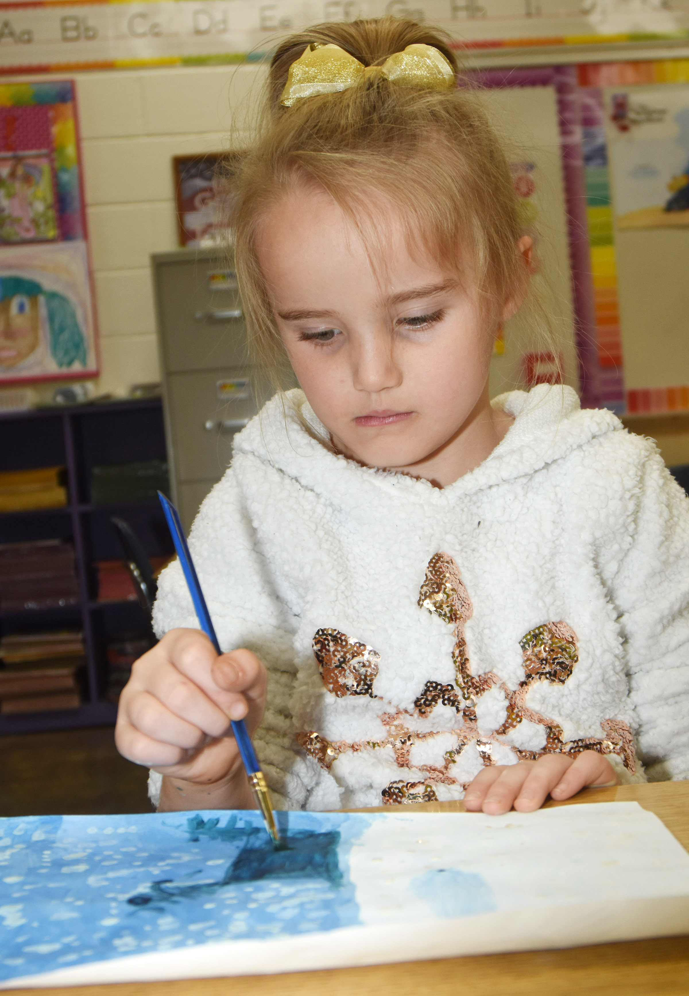 CES first-grader Trinity Dye paints a winter landscape.