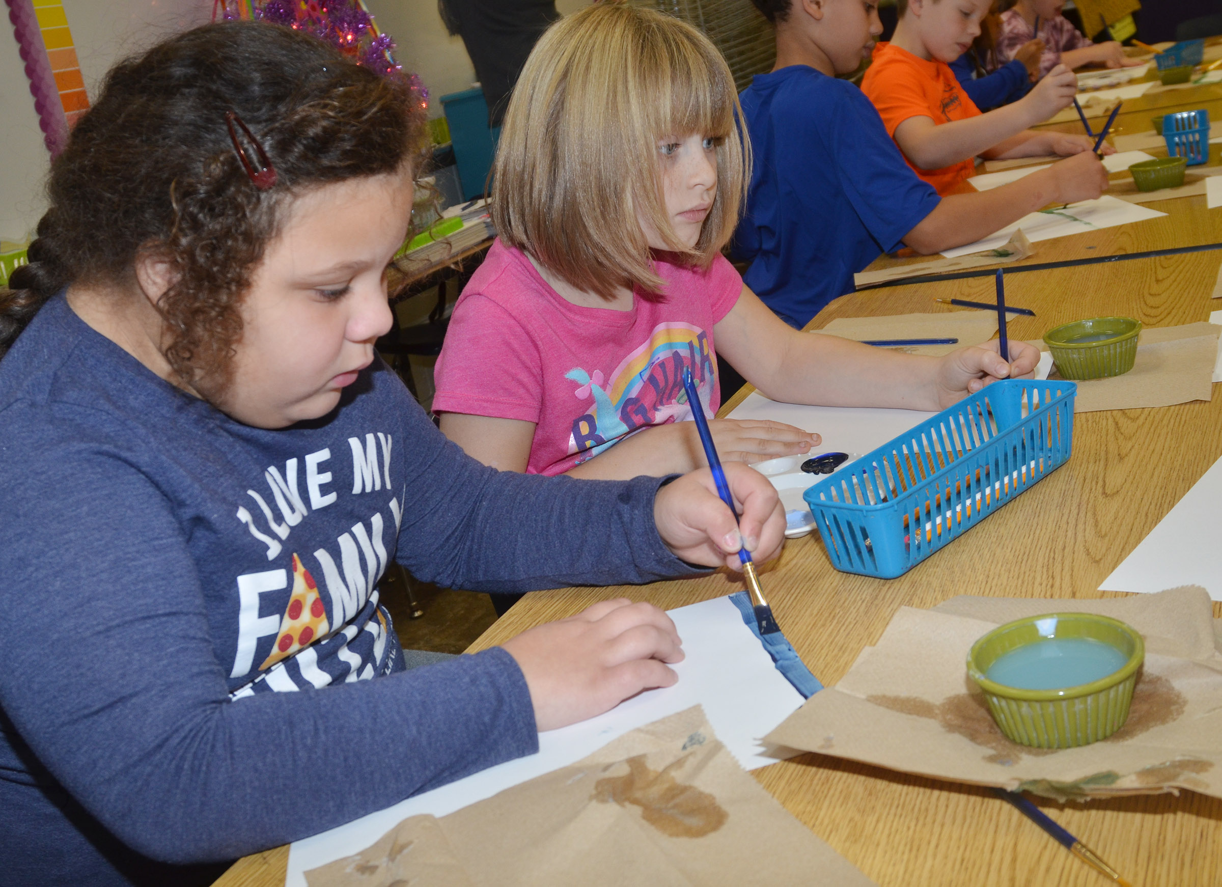 CES second-graders Amylah Taylor, at left, and Summer Daniels paint the sky in their winter scene.