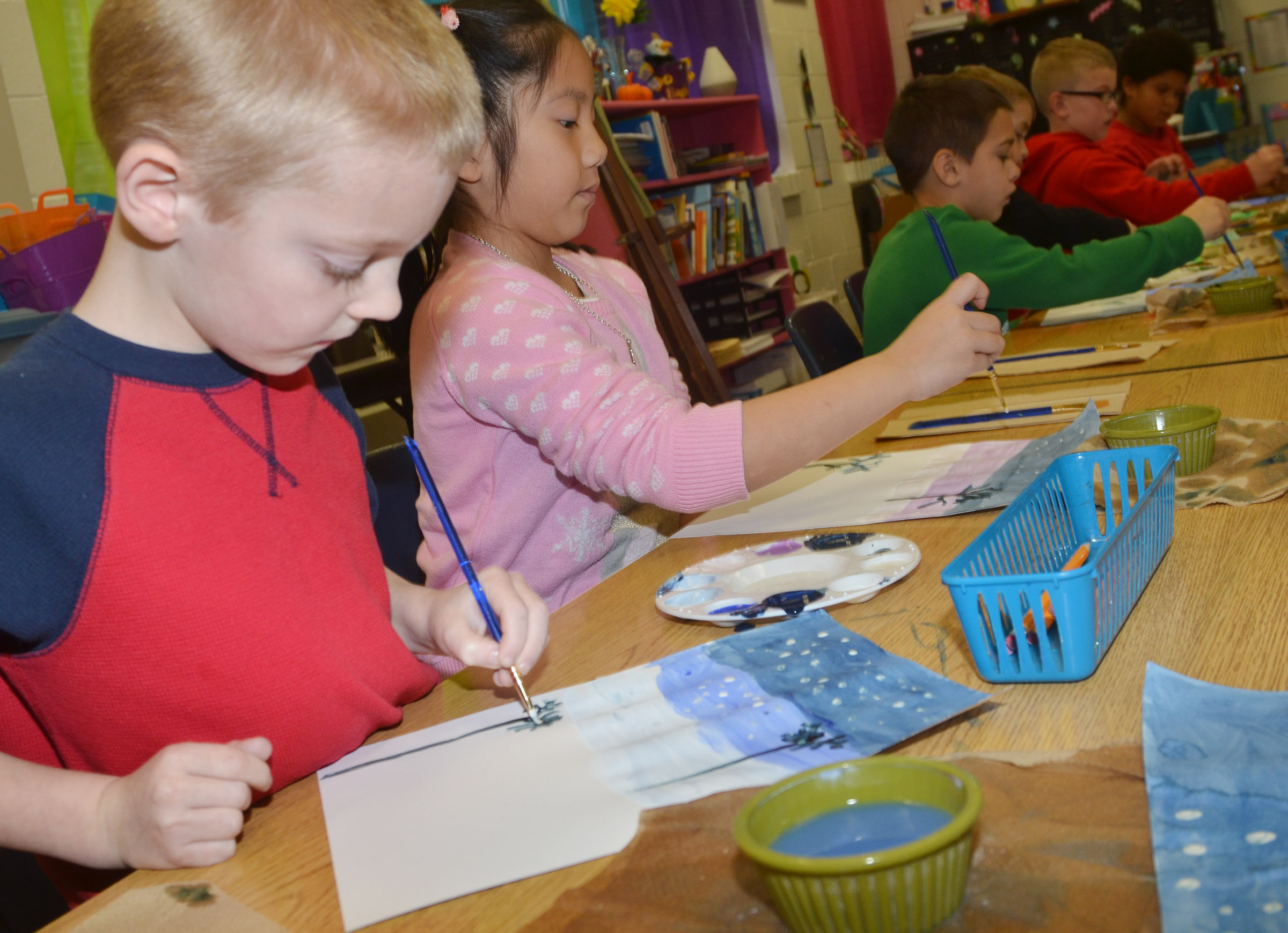 CES second-graders Brandon Thompson, at left, and Tina Jiang paint their winter scenes.