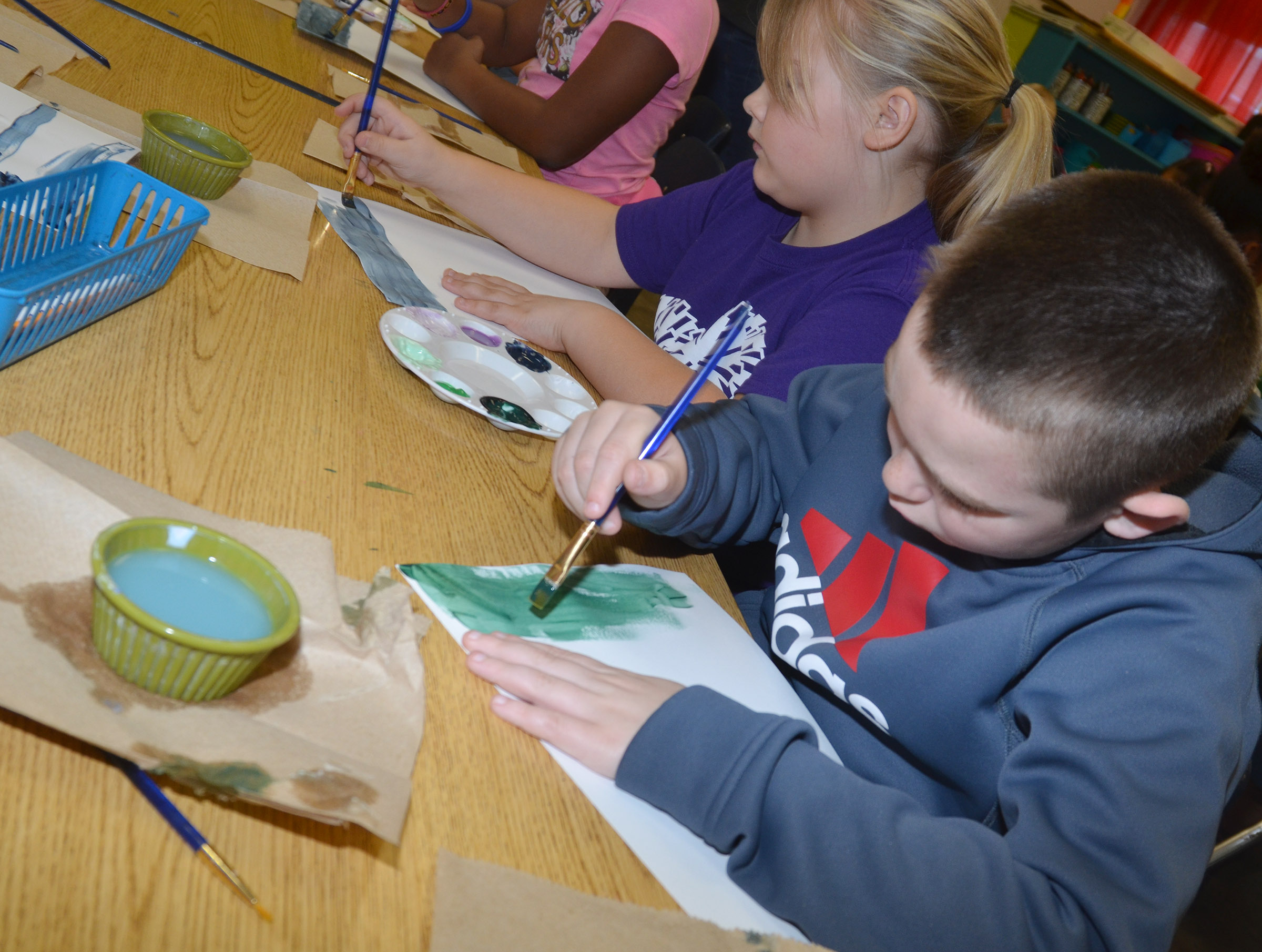 CES second-graders Addysen England, at left, and Colton Maggard paint the sky in their winter scene.