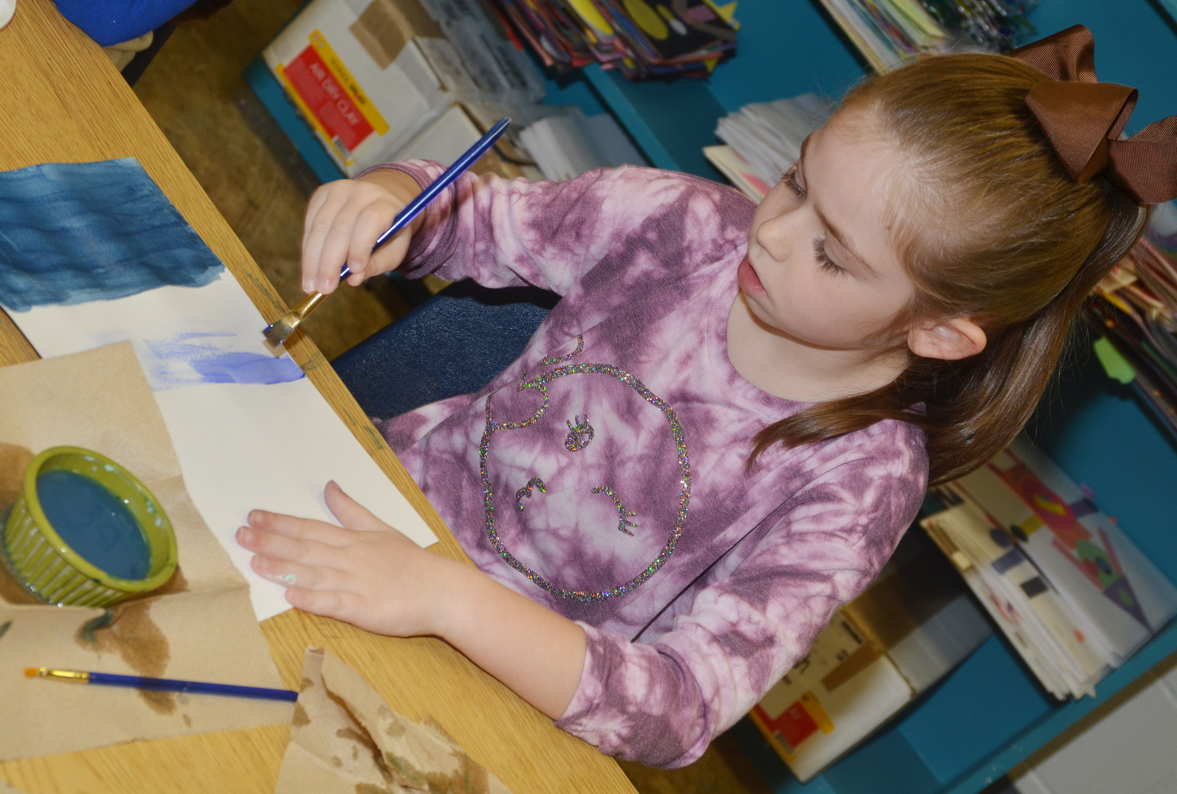 CES second-grader Lainey Price paints her winter scene.