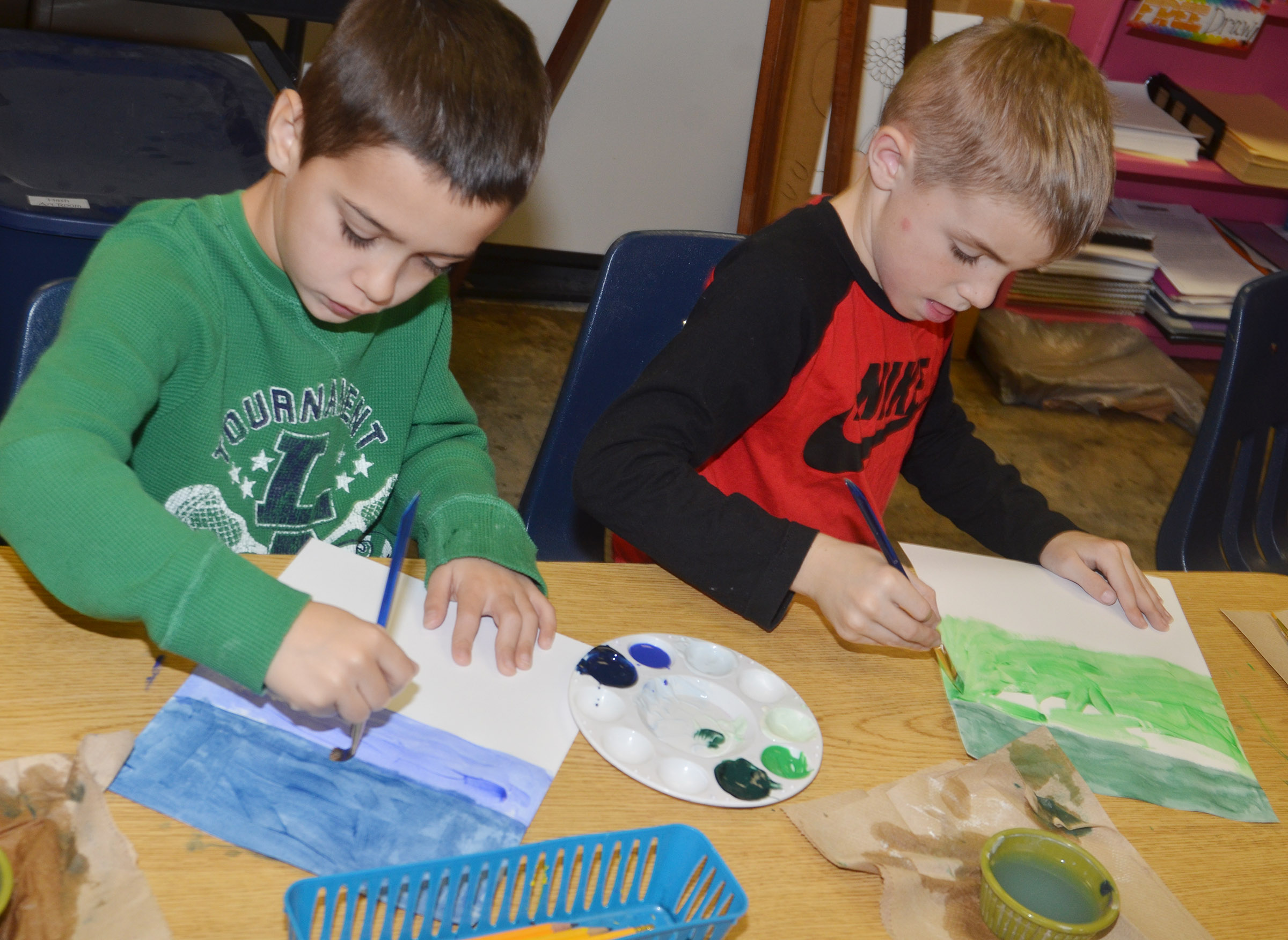 CES second-graders Brenden Chastain, at left, and Ben Lord paint their winter scenes.