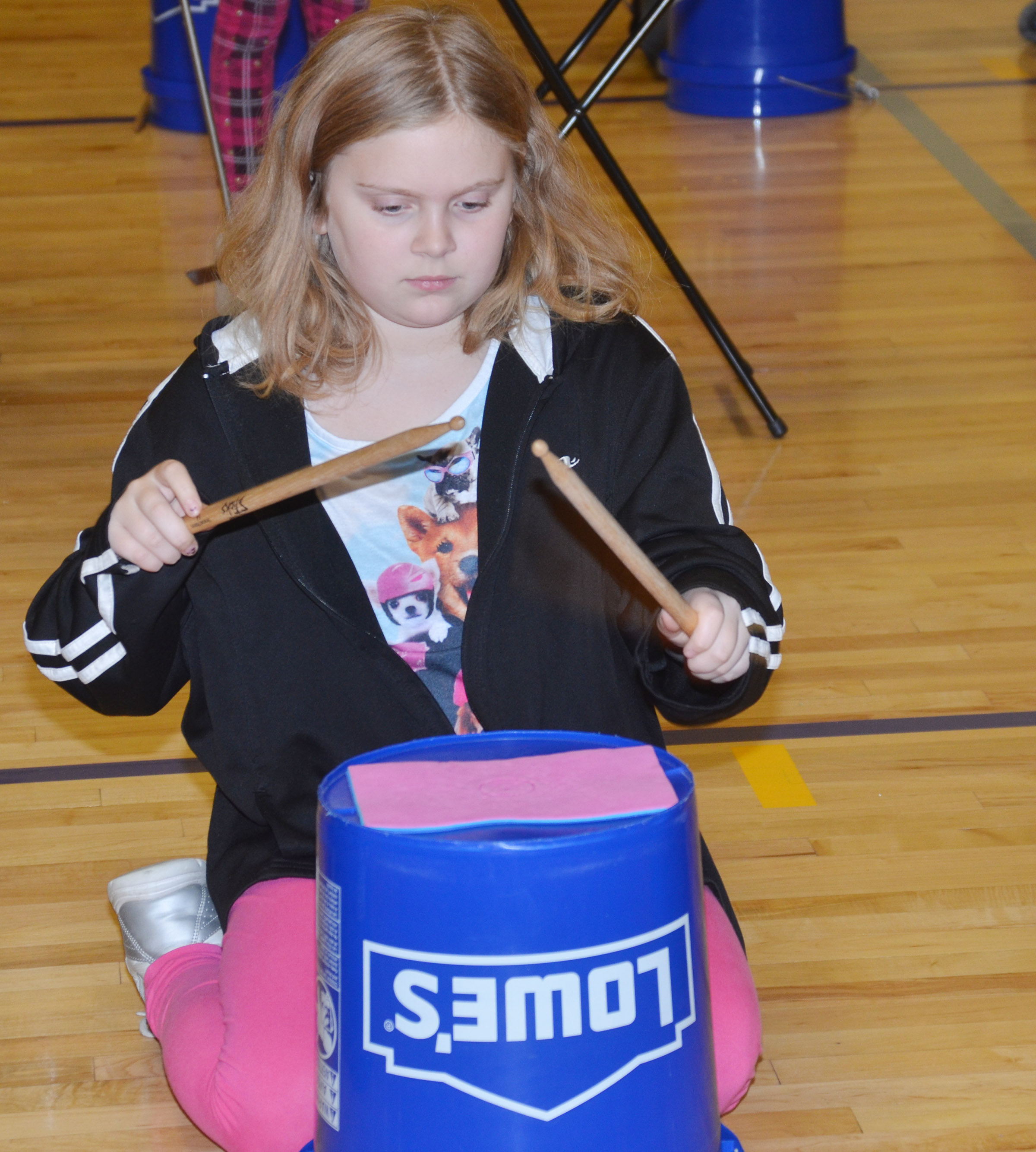 CES fourth-grader Arianna Childers plays the bucket drums.