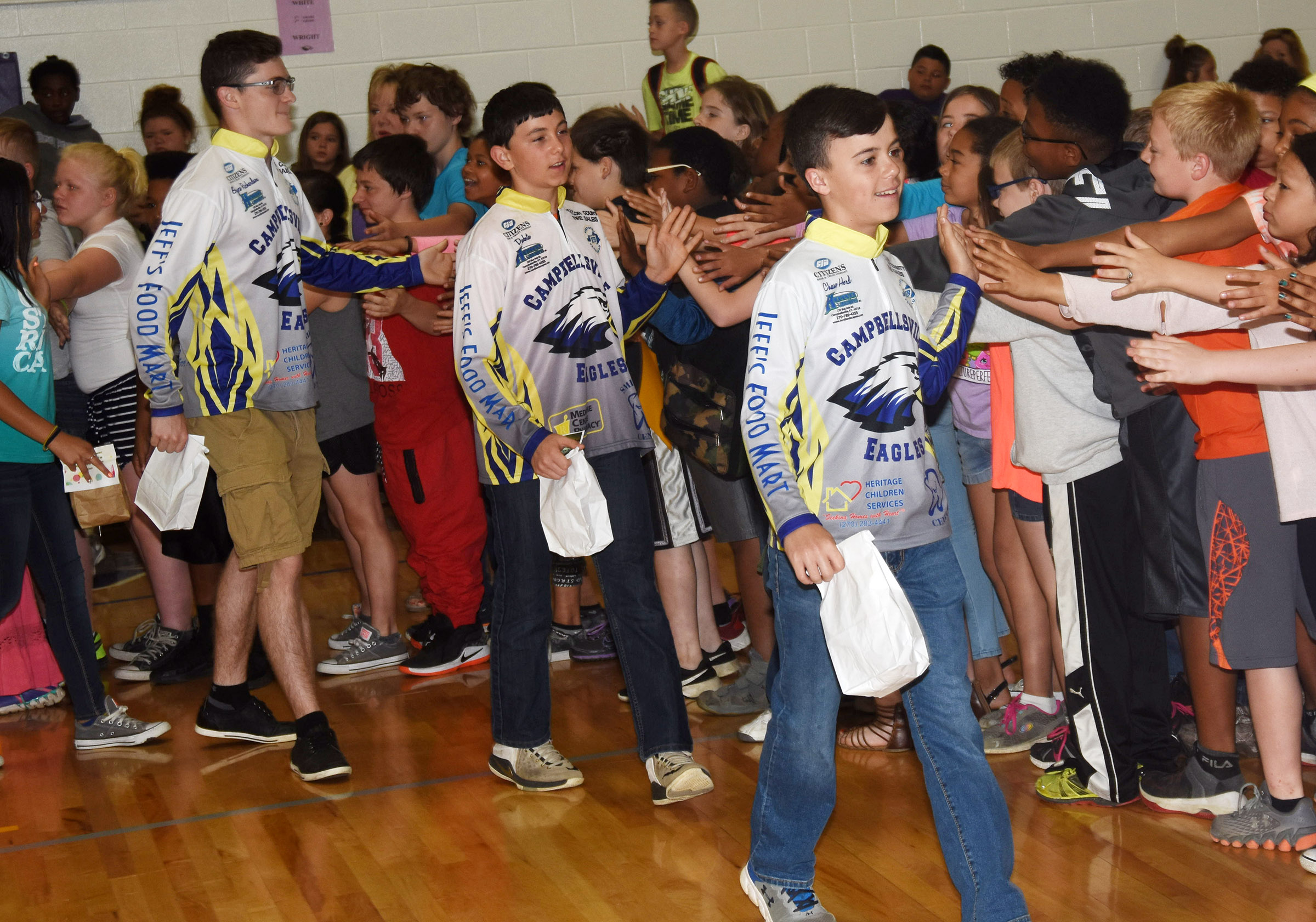 CHS fishing team members high-five CES students.