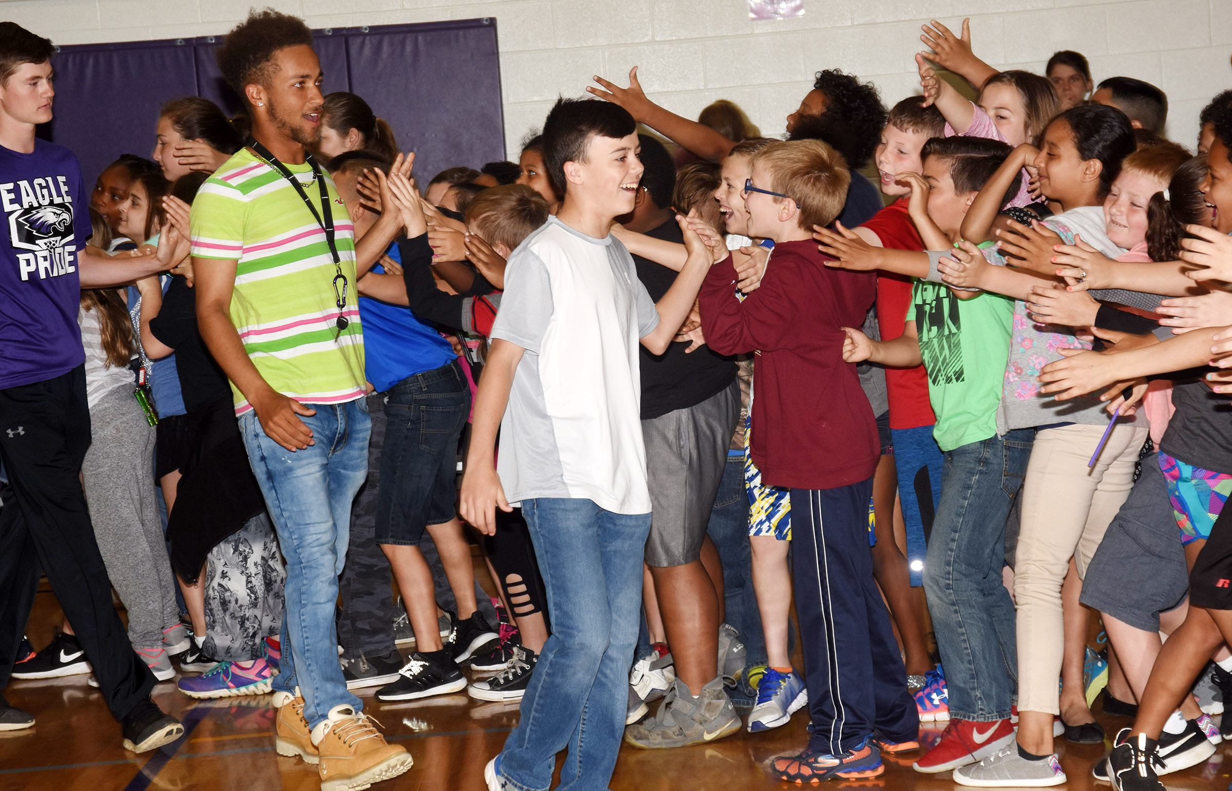 From left, CHS freshman Tristin Faulkner, CHS senior Ethan Lay and CMS seventh-grader Chase Hord high-fives CES students.