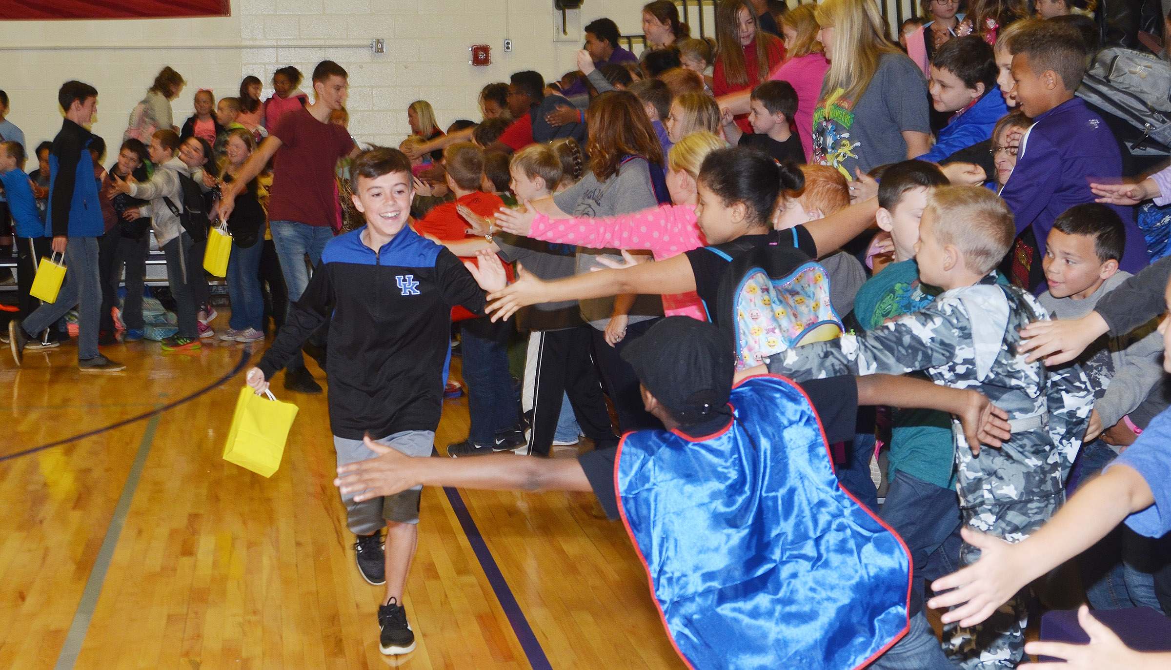 CHS cross country runners high-five CES students.