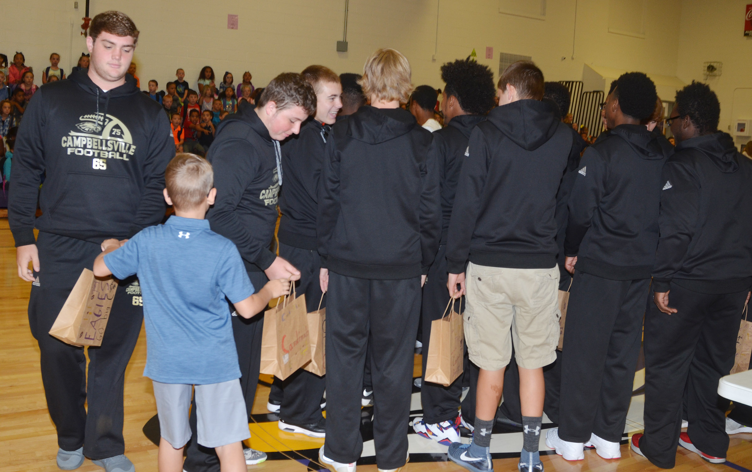 CHS football players receive treats from CES fourth-grader Cameron Estes.