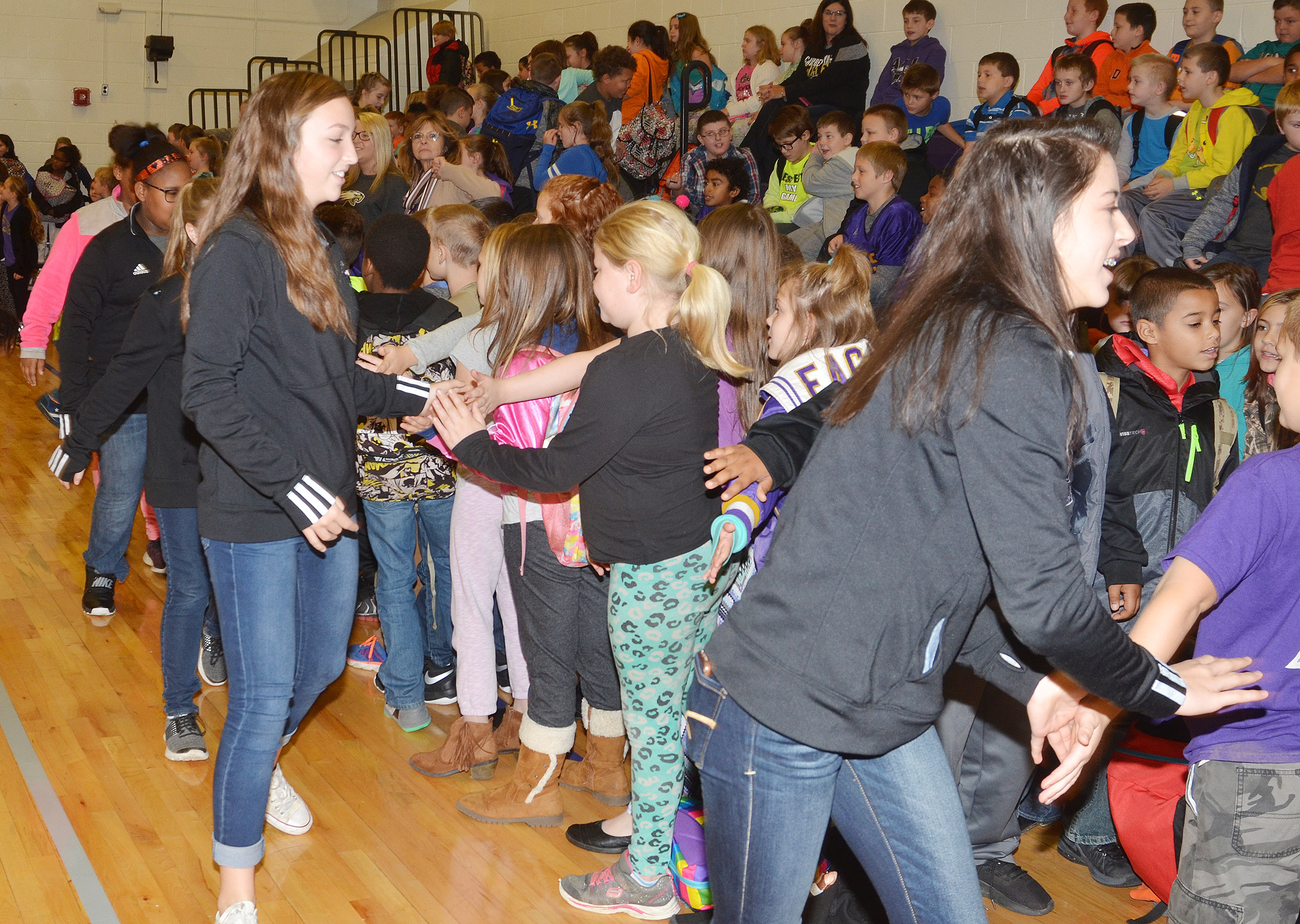 CMS girls' basketball players give high-fives to CES students.