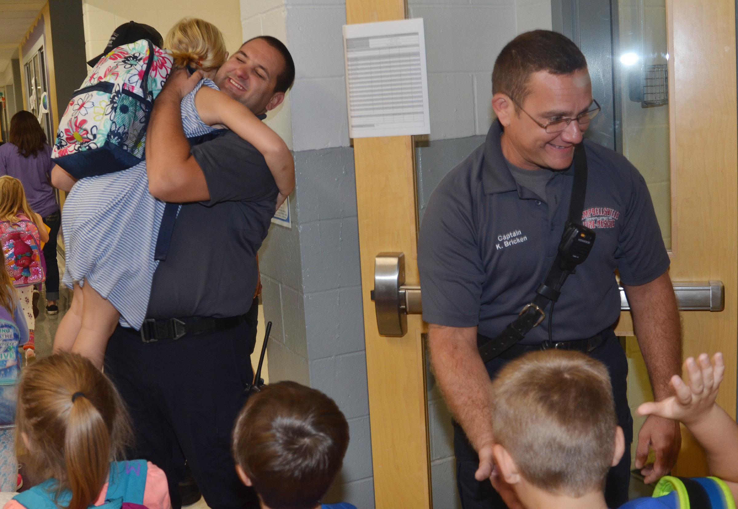 Campbellsville Fire & Rescue Captain Keith Bricken greets CES students while firefighter Alex Johnson picks up and hugs kindergartener Remi Petett.