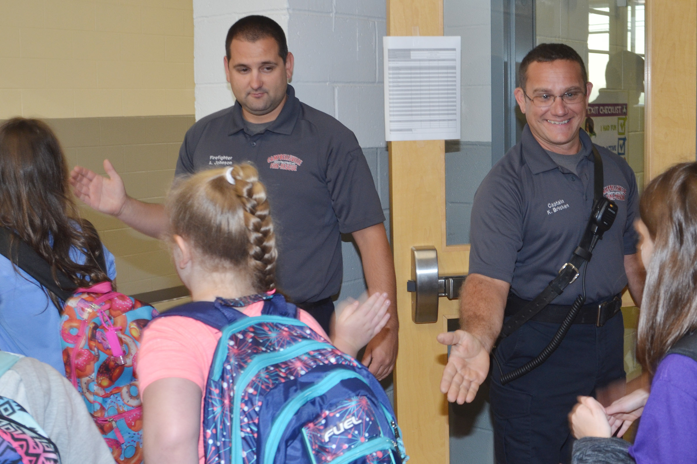 Campbellsville Fire & Rescue Captain Keith Bricken, at right, and firefighter Alex Johnson greet CES students.