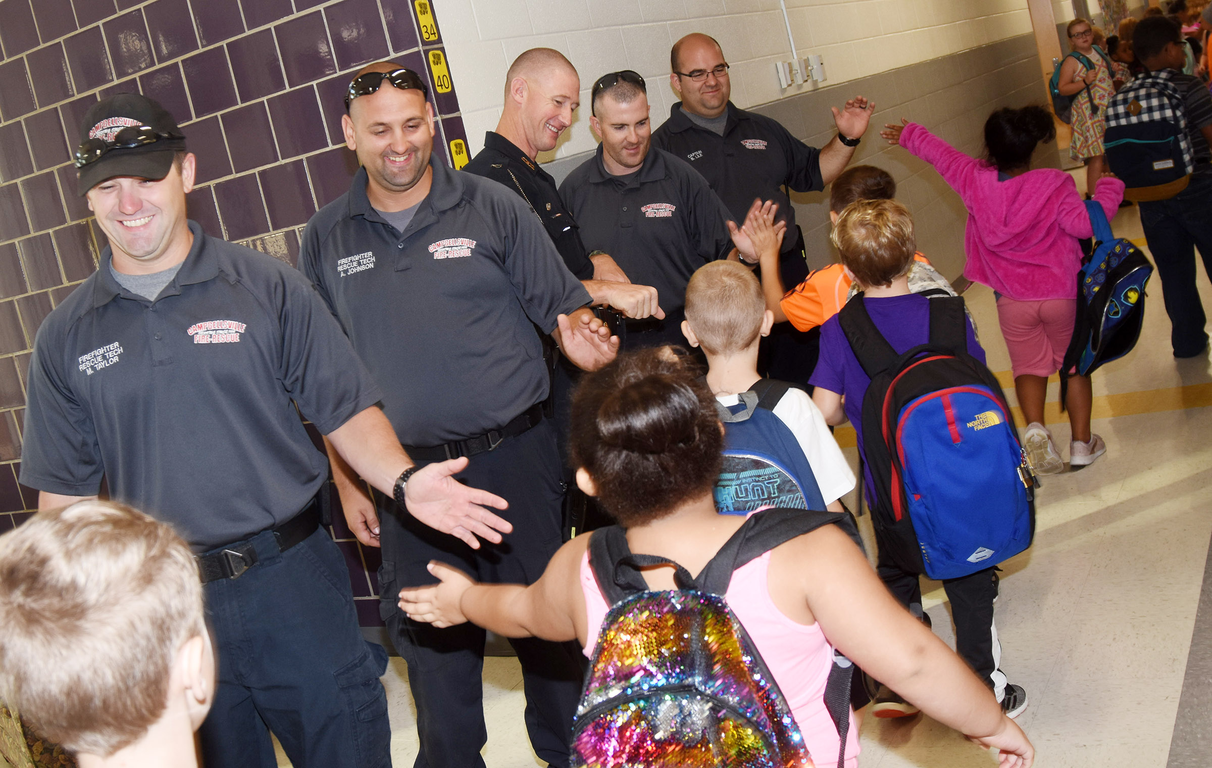 From left, Campbellsville Fire & Rescue personnel Matthew Taylor and Alex Johnson, CIS School Resource Officer Charlie Houk and Fire & Rescue personnel Cole Warf and Brent Lile high five and fist bump CES students.