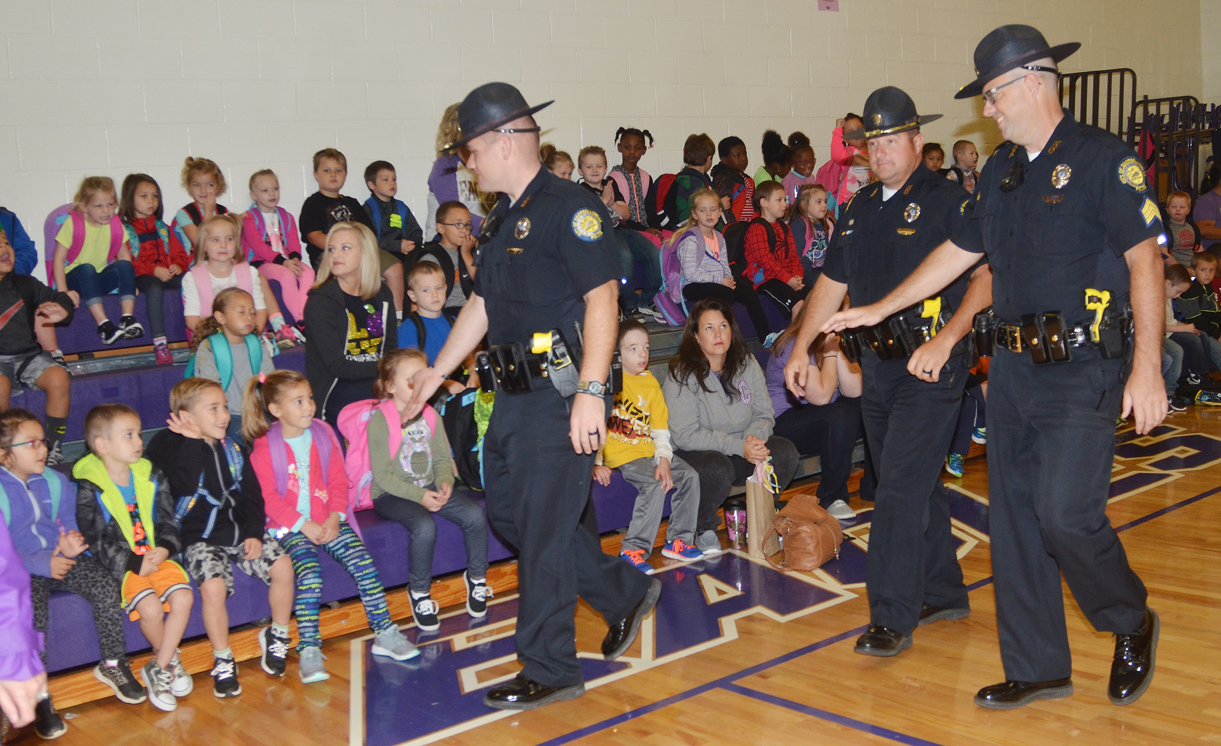 From left, Campbellsville Police officers Jake Hedgespeth, Ryan Jewell and David Tucker greet CES students during their Friday morning assembly.