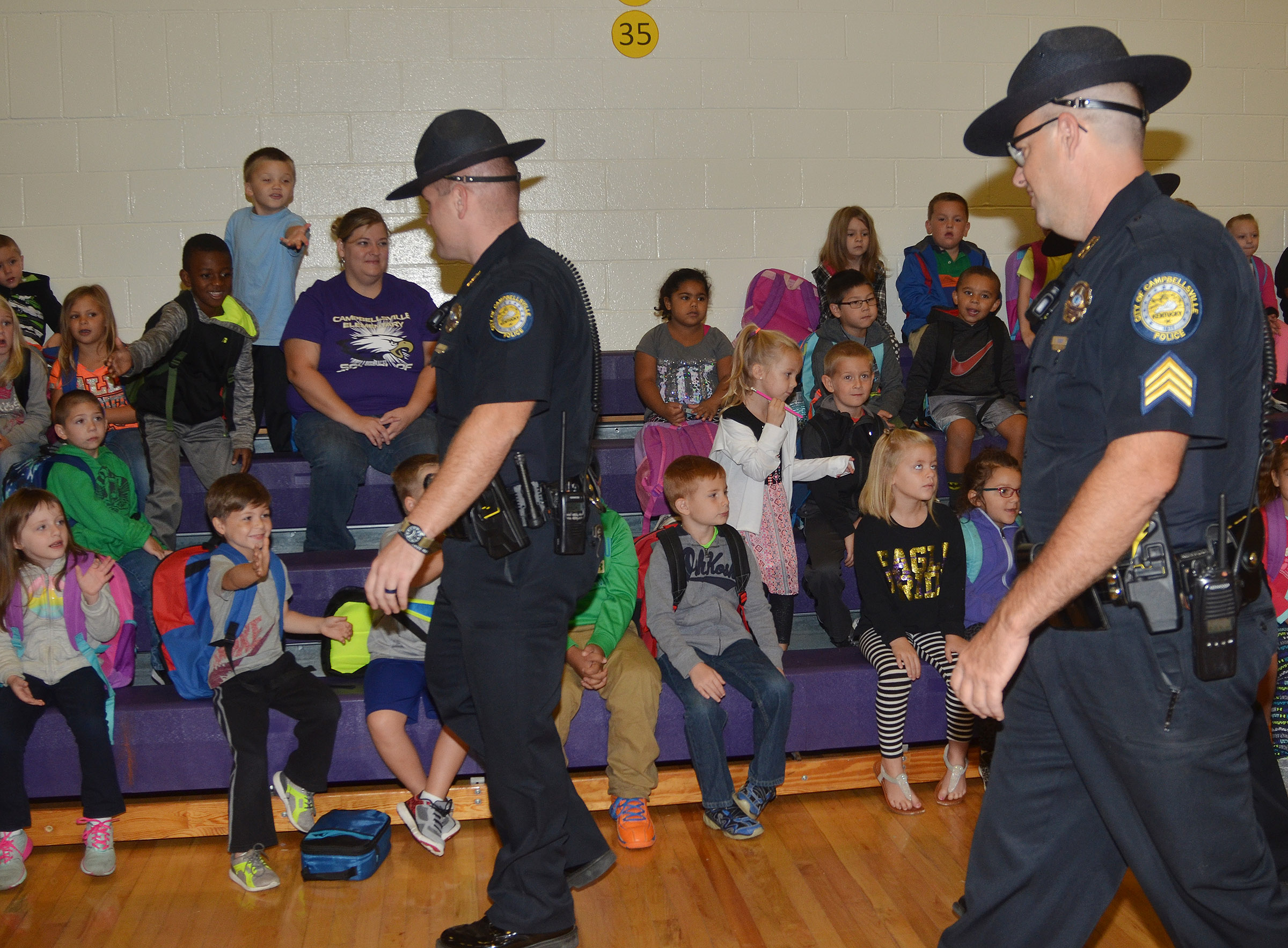 Campbellsville Police officers Jake Hedgespeth, at left, and David Tucker greet CES students during their Friday morning assembly.