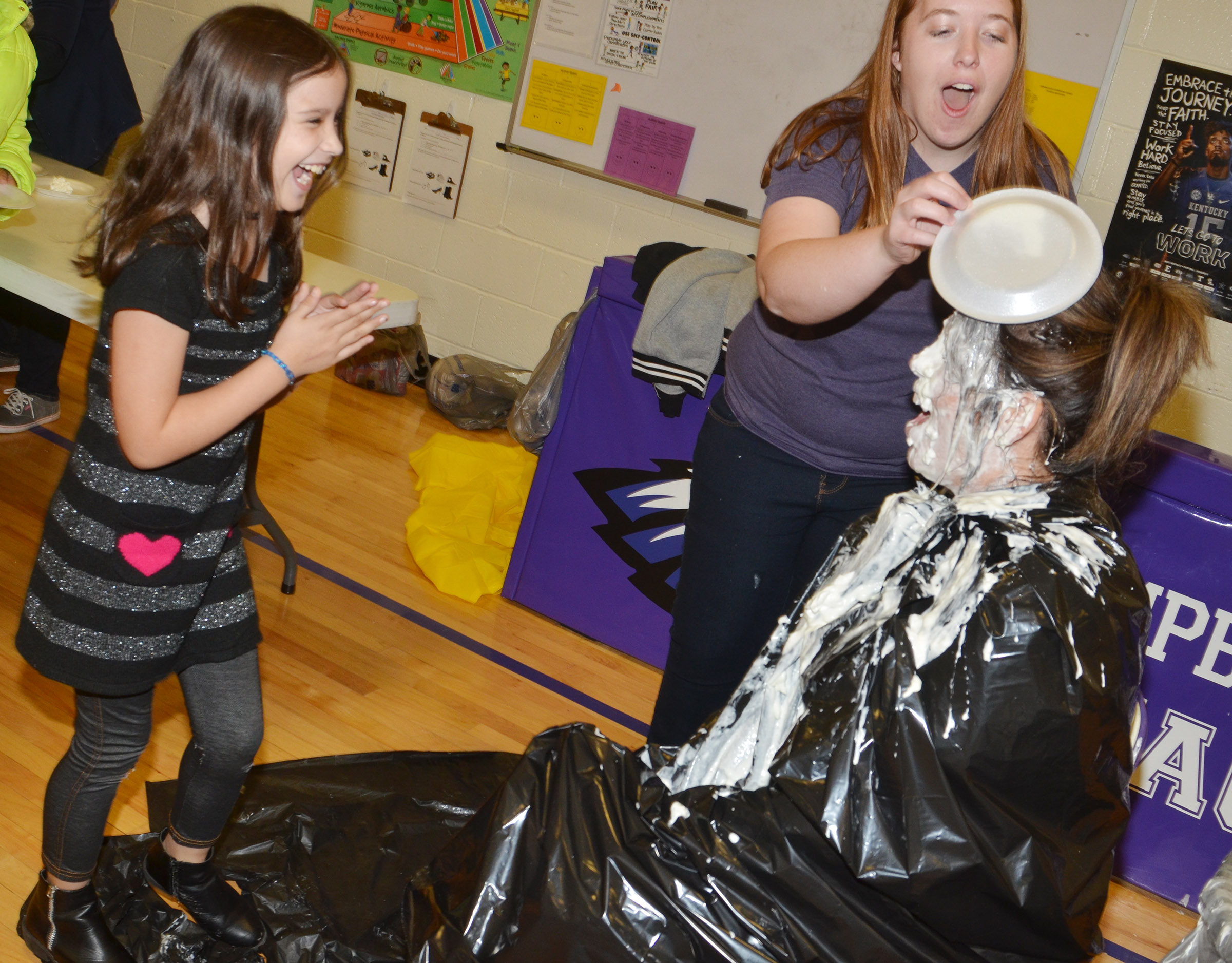 CES fourth-grader Zehavah Negron laughs after hitting Principal Elisha Rhodes with a pie.