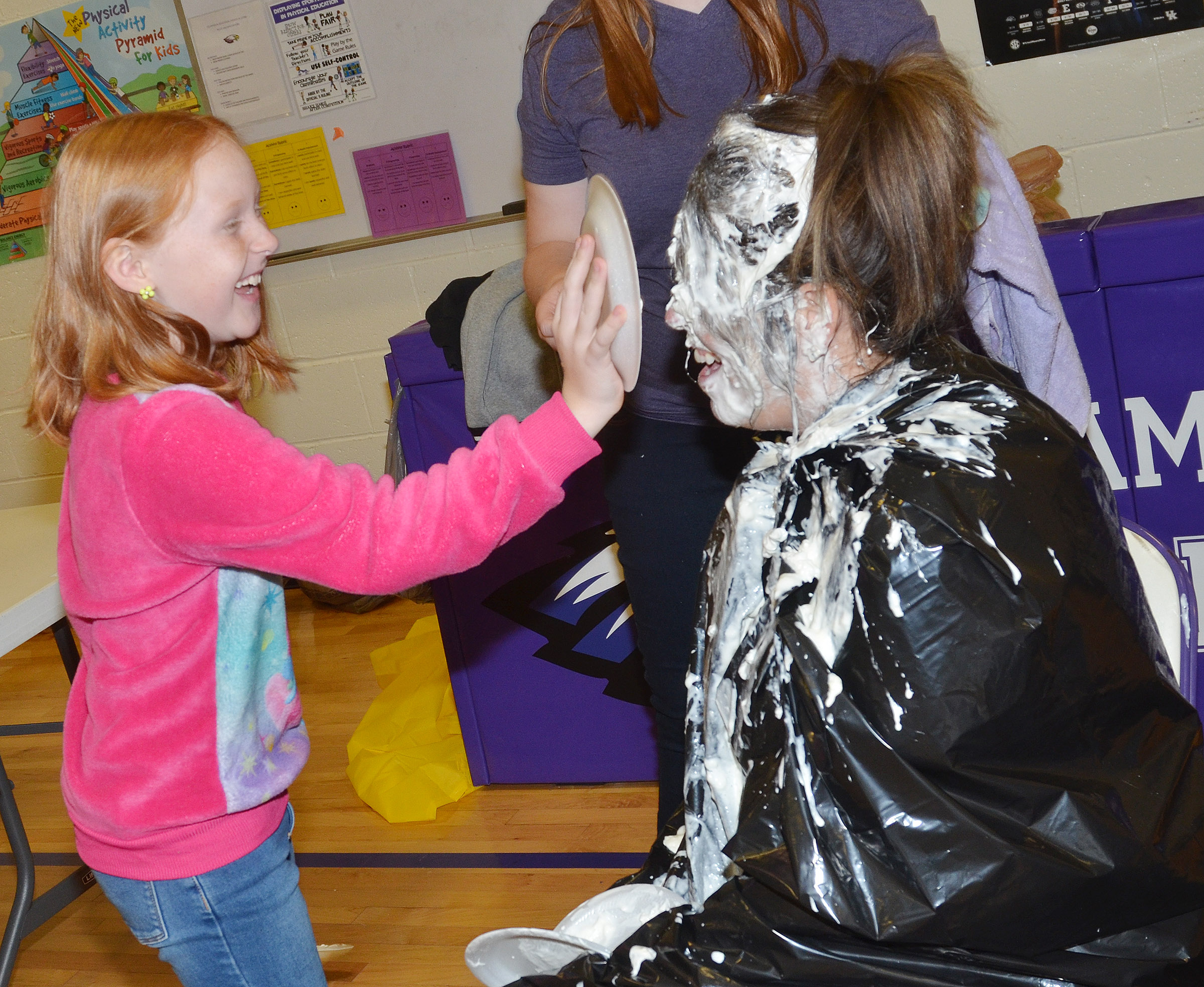 CES fourth-grader Nora Harris pies Principal Elisha Rhodes in the face.