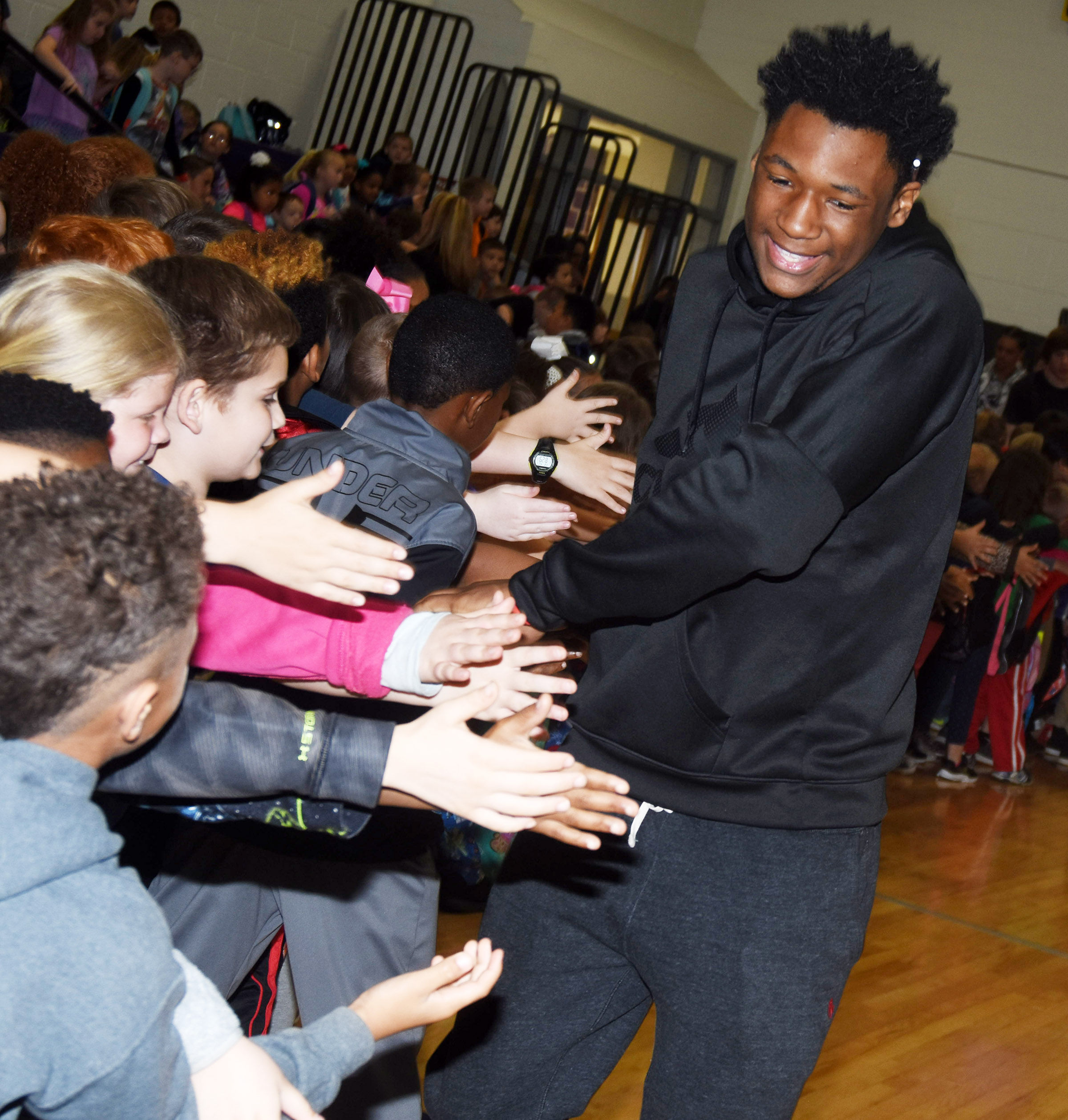 CHS junior and track team members Taj Sanders high-fives CES students.