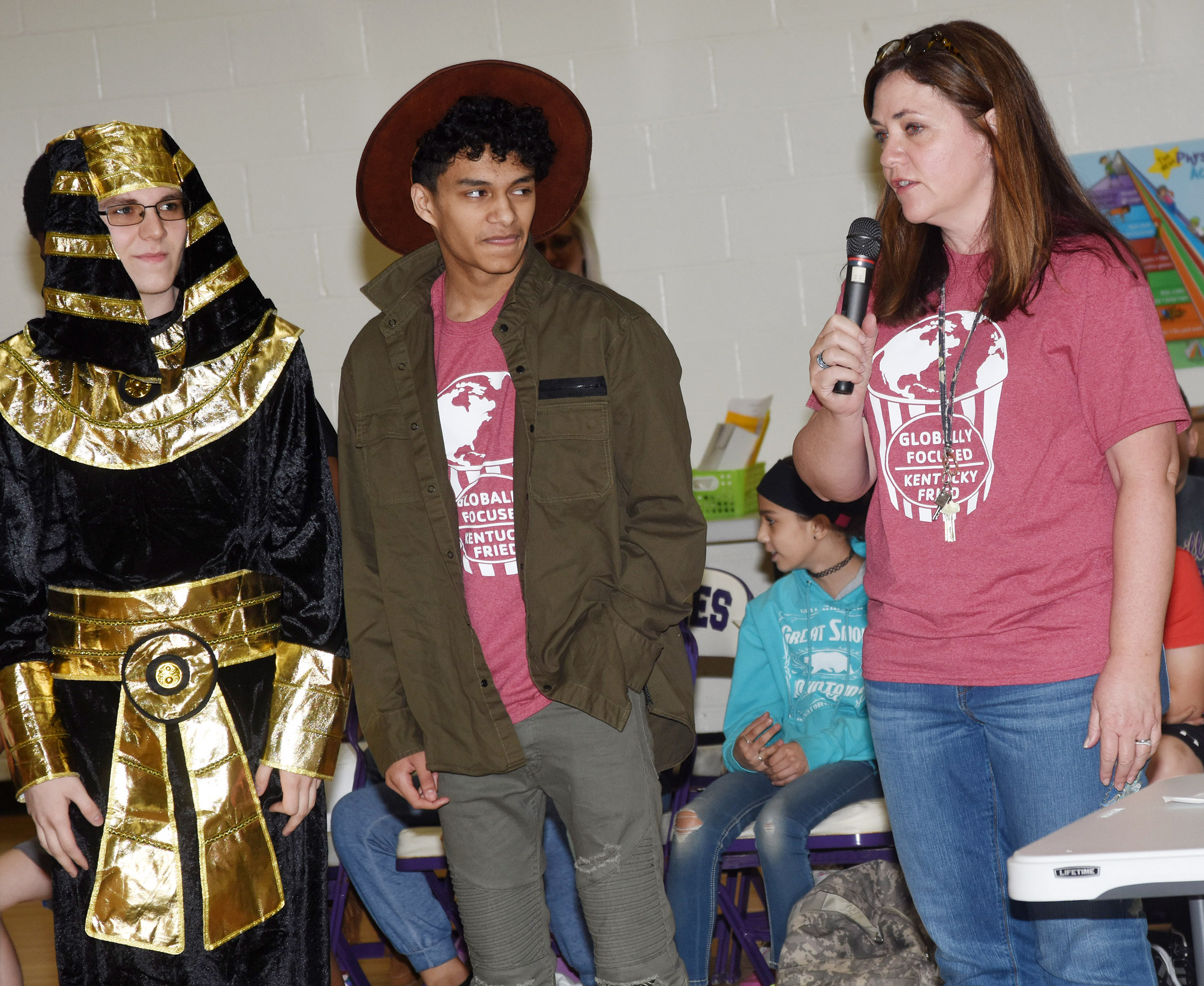 CHS Y-Club sponsor Susan Dabney talks to CES students about her club. At left are junior Brandon Greer and sophomore Ben Arachi, who are dressed in their costumes for their cultural display.