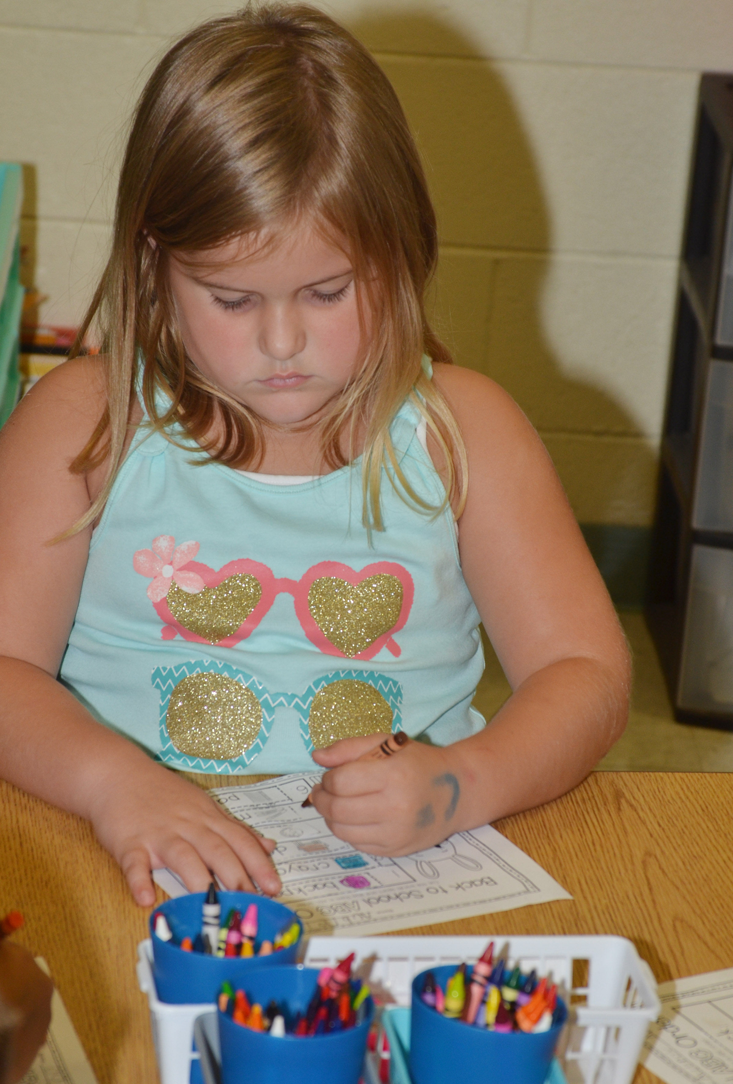 CES first-grader Aubreigh Knifley colors her worksheet.